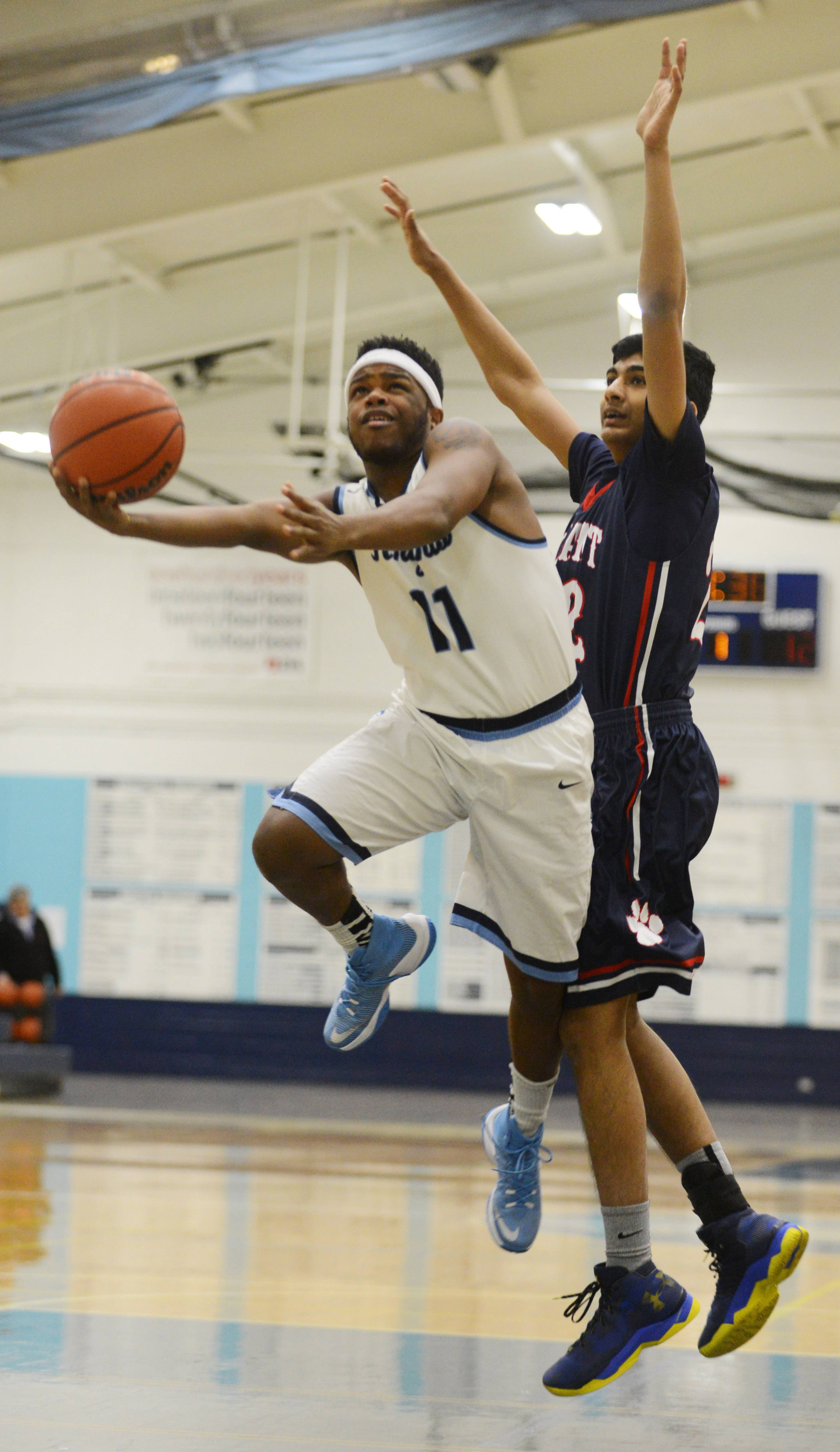 Prospect's Antonio Gardner drives past Conant's Raja Mittal for a layup during Tuesday's game in Mount Prospect.