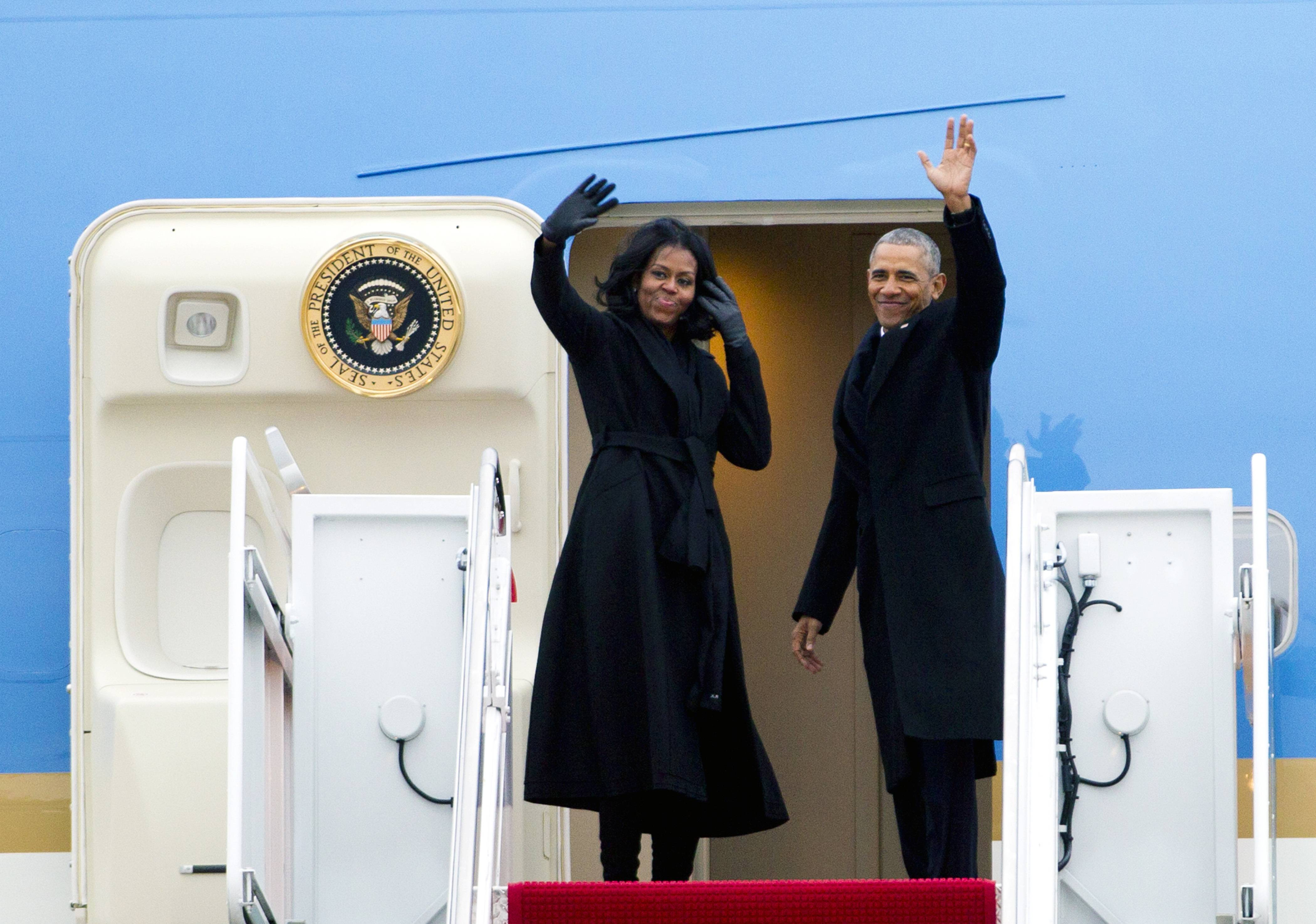 President Barack Obama and first lady Michelle Obama wave from Air Force One at Andrews Air Force Base, Maryland, as they leave for Chicago for his presidential farewell address.