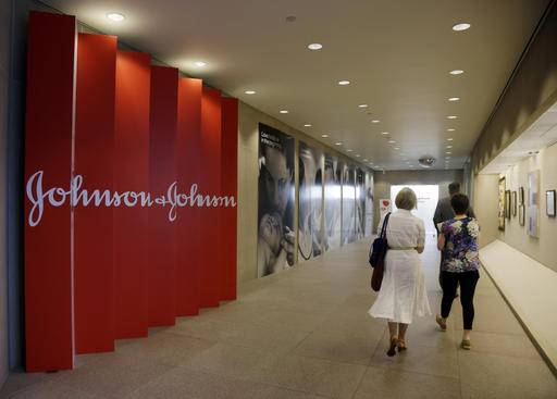 FILE - In this July 30, 2013, file photo, people walk along a corridor at the headquarters of Johnson & Johnson in New Brunswick, N.J. Amid the storm over soaring medicine prices, health care giant Johnson & Johnson says that beginning in February 2017 the company will disclose average increases in the list price and what middlemen actually pay for its prescription drugs. That will help J&J's image more than patients initially, experts say, but it could push other drugmakers to restrain future price increases and be more transparent. (AP Photo/Mel Evans, File)