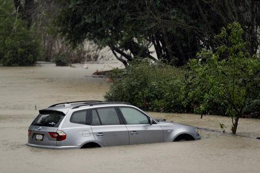 A car is submerged as the Russian River floods Johnson's Beach, Tuesday, Jan. 10, 2017, in Guerneville, Calif. The latest in an onslaught of winter storms comes with blizzard warnings for the Sierra Nevada and a new round of flooding for Northern California river towns where thousands of people remained under evacuation advisory Tuesday. (AP Photo/Eric Risberg)