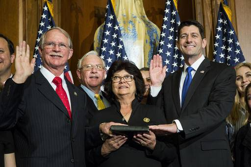 FILE - In this Jan. 3, 2017, file photo, House Speaker Paul Ryan of Wis. administers the House oath of office to Rep. John Rutherford, R-Fla., during a mock swearing in ceremony on Capitol Hill in Washington. Rutherford was wheeled out of the Capitol on a stretcher on Jan. 11. His office did not immediately return requests inquiring about his condition. (AP Photo/Zach Gibson, File)
