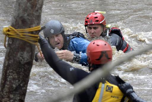 Jason Williams, left, is rescued by Calfire rescue swimmer Danny Ciecek after Williams got snagged on trees while trying to kayak the Carmel River with a friend near Paso Hondo Road in Carmel Valley on Monday, Jan. 9, 2017, after a large storm passed through Monterey County. (David Royal/The Monterey County Herald via AP)