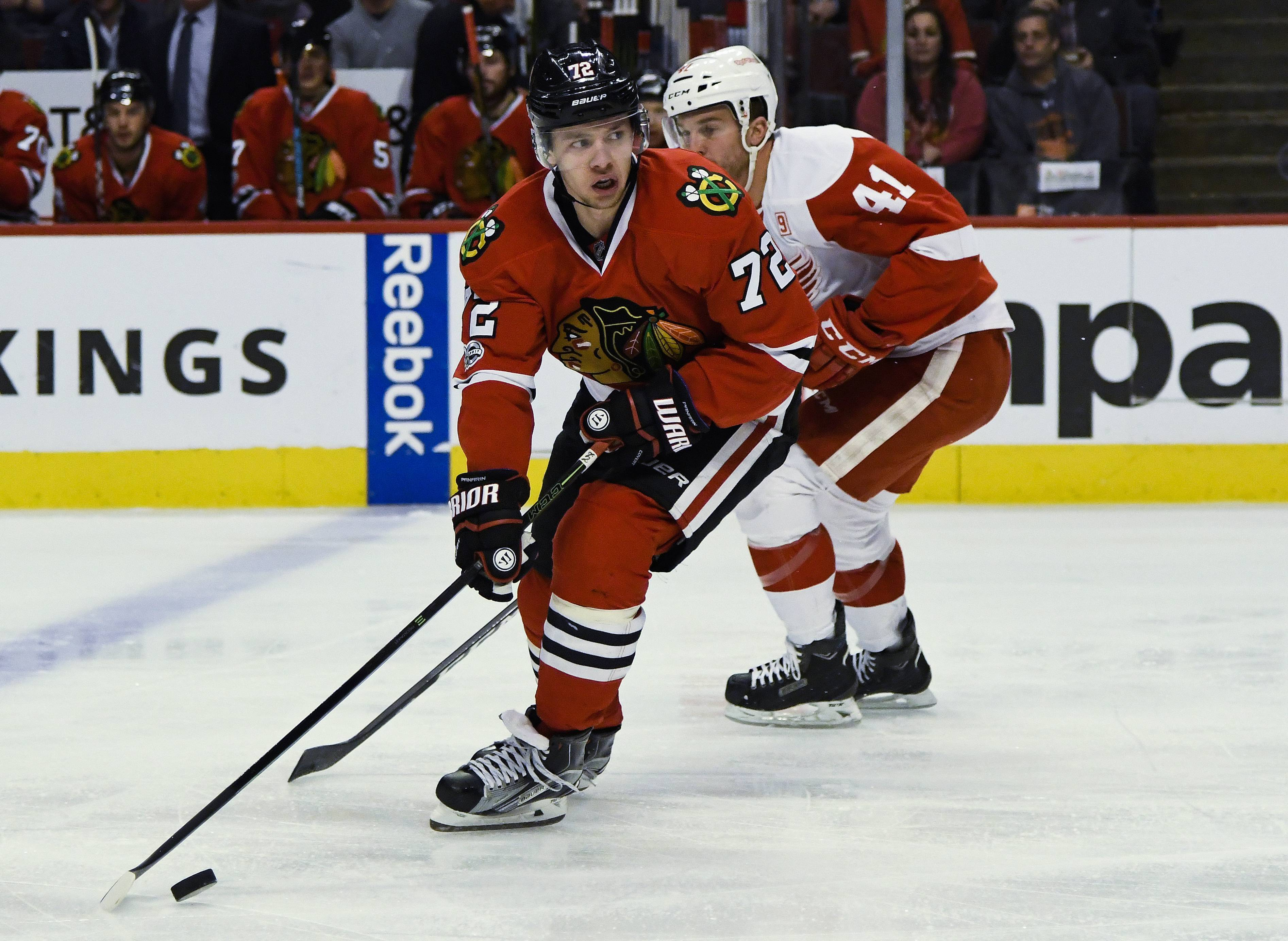 Chicago Blackhawks left wing Artemi Panarin (72) looks to pass the puck against Detroit Red Wings center Luke Glendening (41) during the first period of an NHL hockey game Tuesday, Jan. 10, 2017, in Chicago.