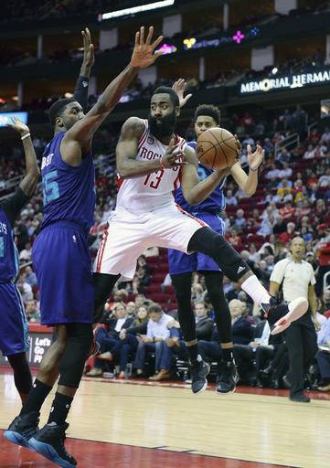 Houston Rockets guard James Harden (13) passes as he drives between Charlotte Hornets center Roy Hibbert (55) and Jeremy Lamb, right, in the second half of an NBA basketball game on Tuesday, Jan. 10, 2017, in Houston. (AP Photo/George Bridges)