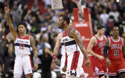 Washington Wizards guard John Wall (2) reacts after he scored during the closing seconds of an NBA basketball game against the Chicago Bulls, Tuesday, Jan. 10, 2017, in Washington. Also seen is Chicago Bulls guard Rajon Rondo (9) and Washington Wizards forward Kelly Oubre Jr. (12). The Wizards won 101-99. (AP Photo/Nick Wass)