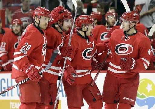 Carolina Hurricanes' Jeff Skinner, second from right, is congratulated by Victor Rask, right, of Sweden, Matt Tennyson (26) and Noah Hanifin, second from left, following Skinner's goal during the second period of an NHL hockey game against the Columbus Blue Jackets in Raleigh, N.C., Tuesday, Jan. 10, 2017. (AP Photo/Gerry Broome)