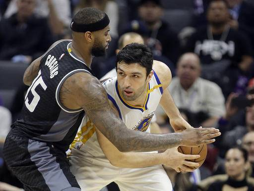 Sacramento Kings forward DeMarcus Cousins, left, guards Golden State Warriors center Zaza Pachulia during the second half of an NBA basketball game Sunday, Jan. 8, 2017, in Sacramento, Calif. The Warriors won 117-106. (AP Photo/Rich Pedroncelli)