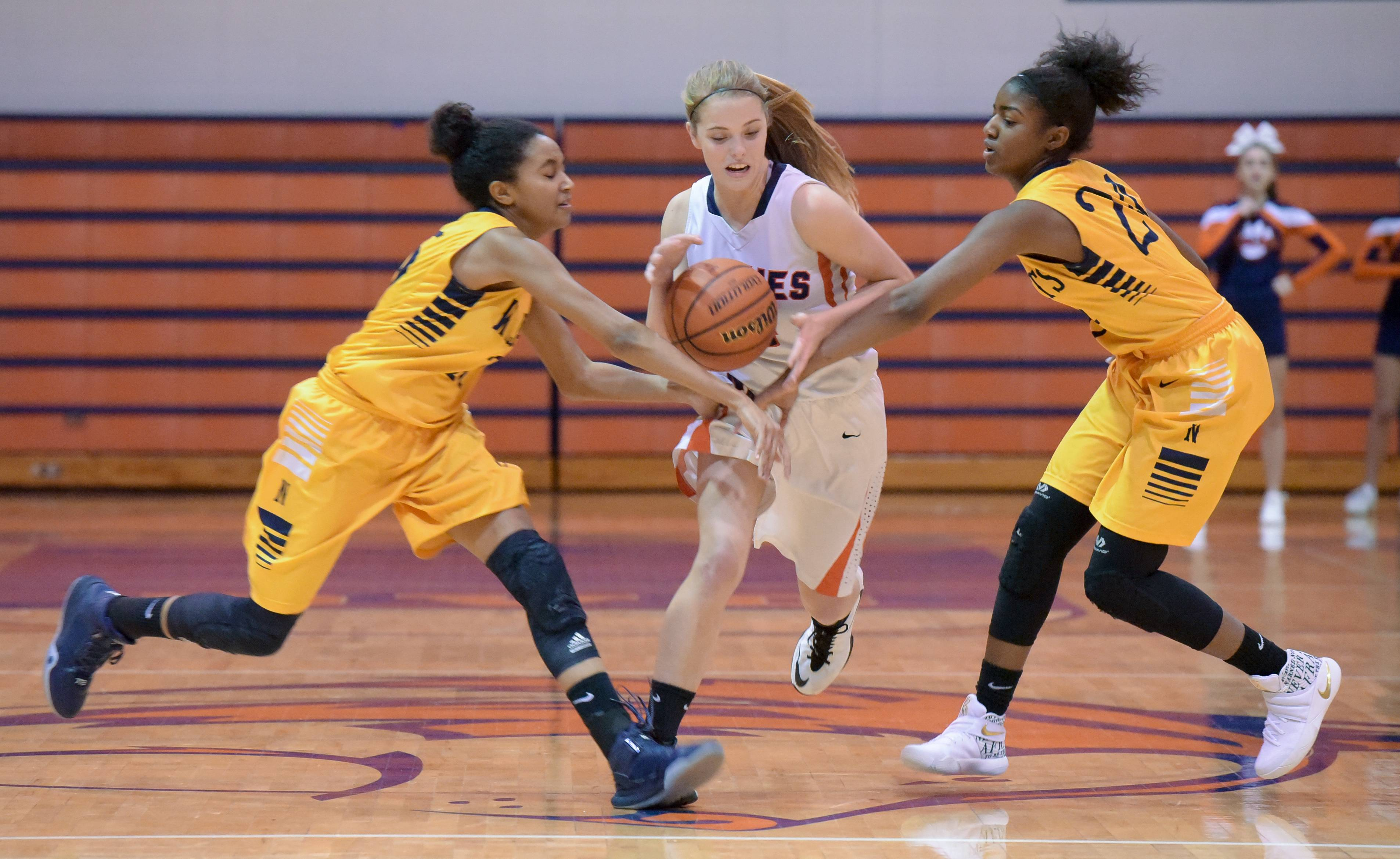 Naperville North's Lauren Platou pushes through Neuqua Valley's Gabby Thomas and Jasmine Walker during girls varsity basketball Wednesday at Naperville North.