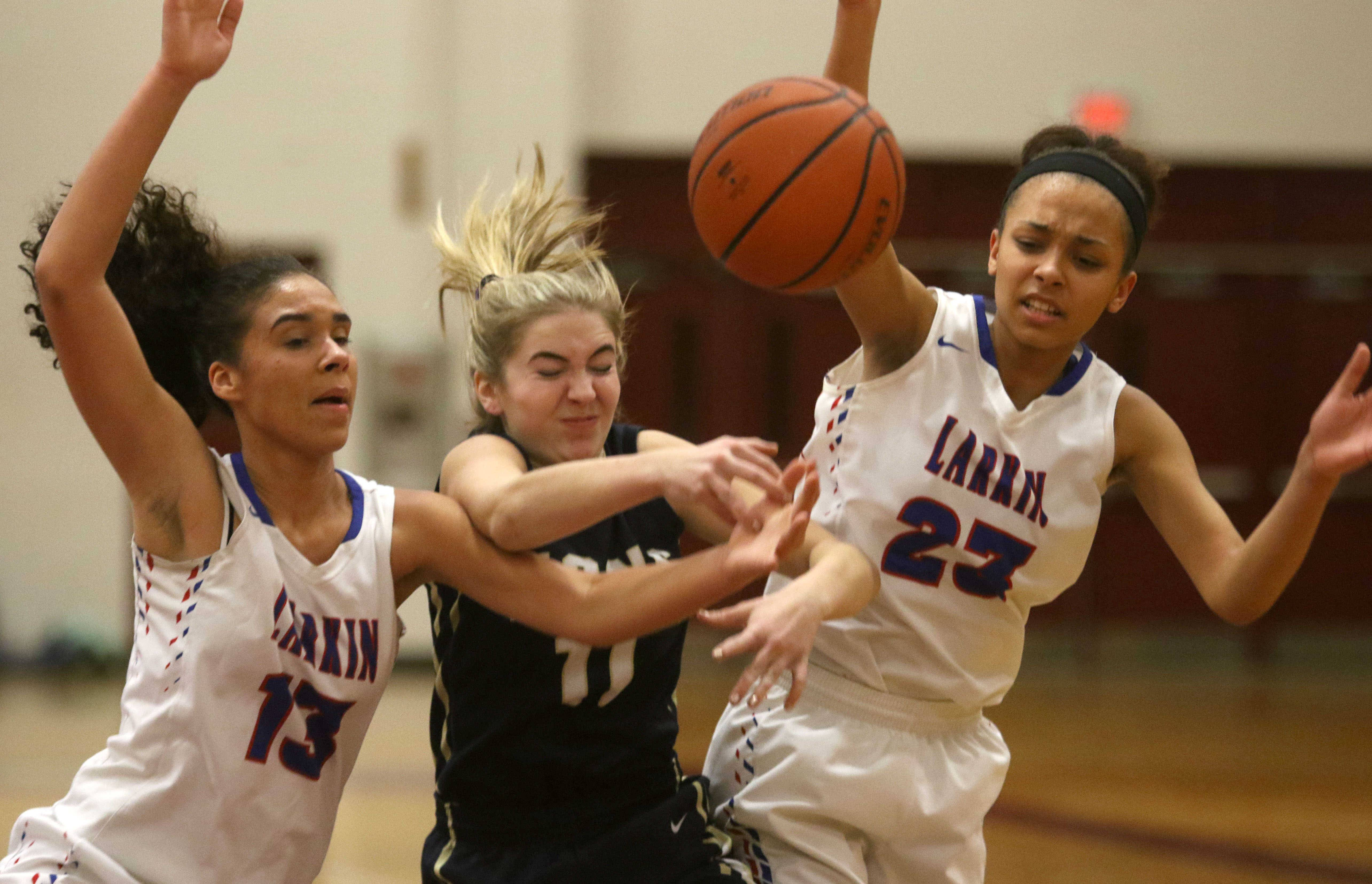 Harvest Christian's Gracie Ozburn, center, gets between Larkin's Brianna Young, left, and Aaliyah Dixon, right, during a varsity girls basketball game as part of the 2017 Elgin City Classic tournament at Chesbrough Field House Wednesday night.