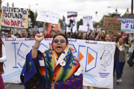 File - In this Jan. 2, 2017 file photo, protesters rally against the Dakota Access Pipeline behind the 128th Rose Parade in Pasadena, Calif. The front lines of the battle against the $3.8 billion Dakota Access pipeline are shifting away from the dwindling encampment in North Dakota.