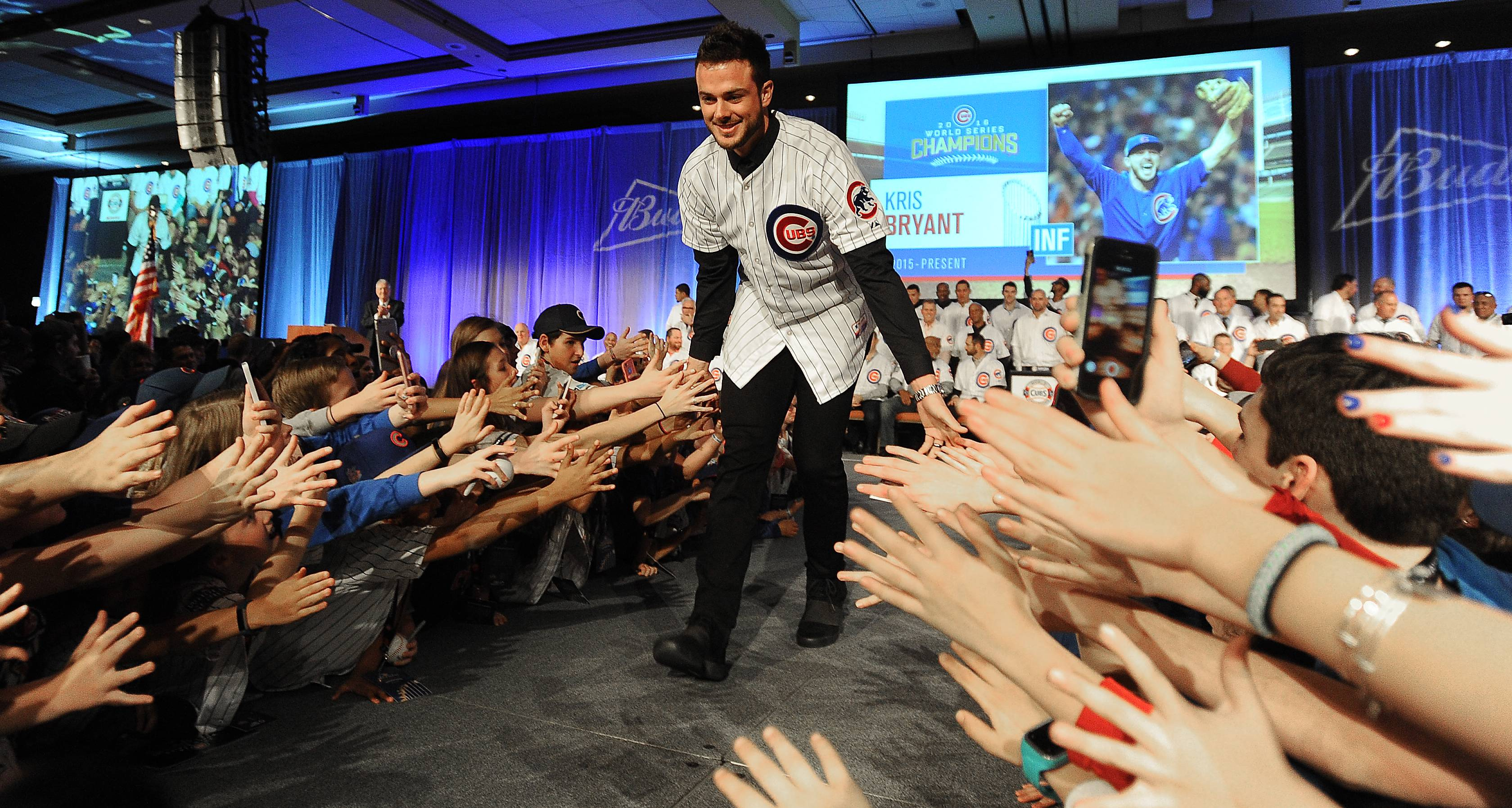 Chicago Cubs player Kris Bryant gets down low with the fans as he takes the stage at the 32nd annual Cubs Convention in Chicago on Friday.