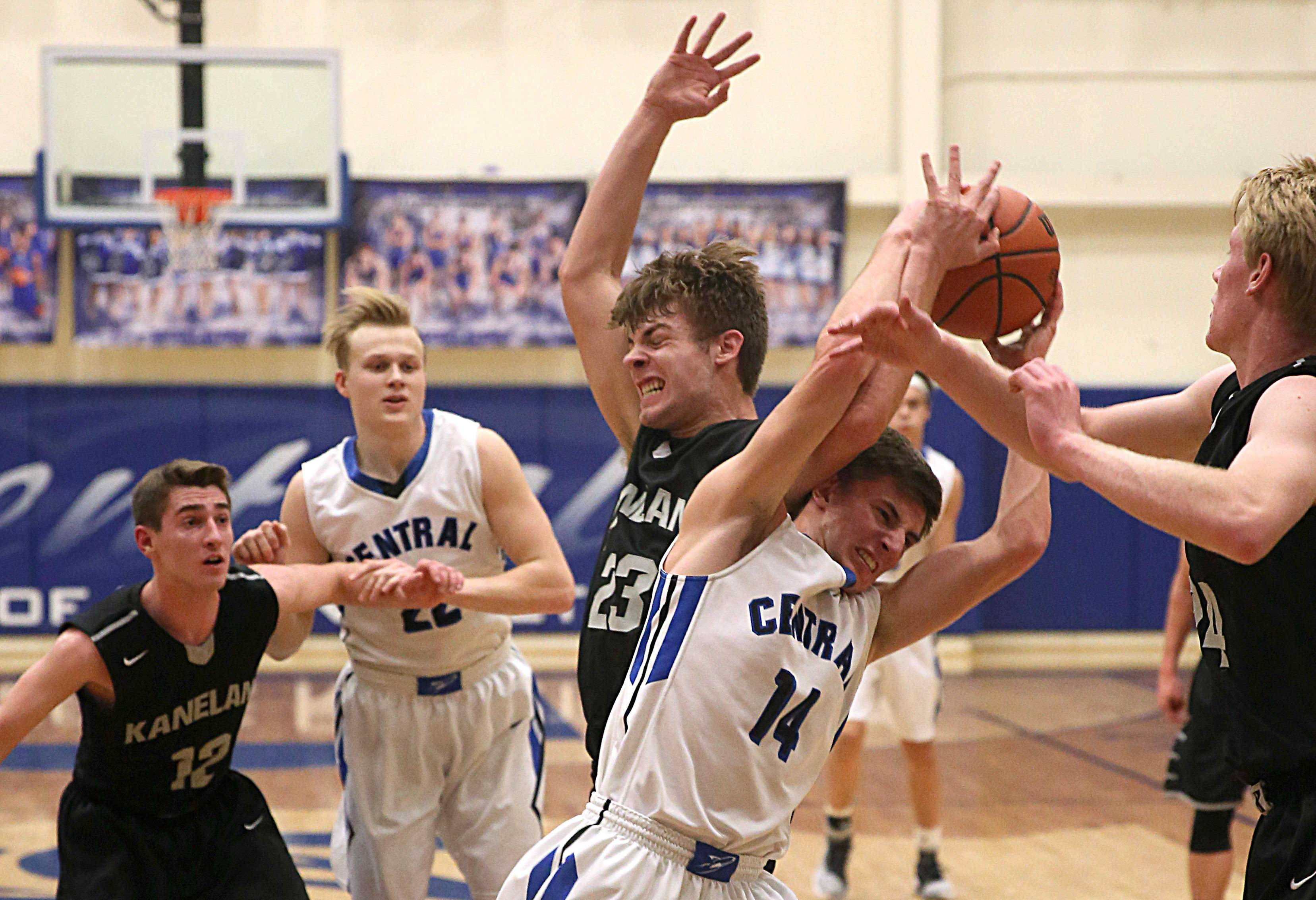 Kaneland's Blake Feiza and Burlington Central's Zach Schutta battle for control of the ball during a varsity boys basketball game as part of the 2017 MLK Classic Basketball Tournament at Central High School Friday night.