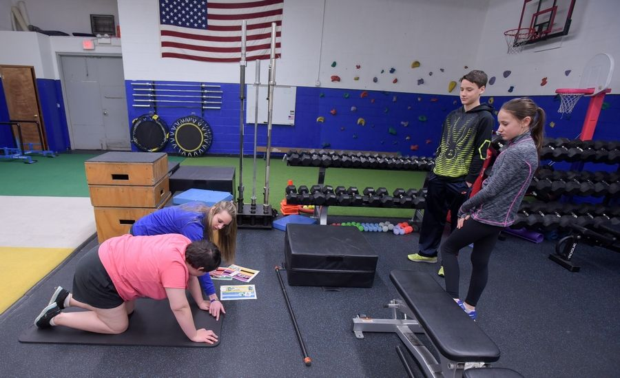 Siblings JP and McKenzie McClear of Hinsdale watch as their 17-year-old sister Courtney, who has autism, works out with fitness specialist Becca Brabec at Right Fit in Willowbrook.