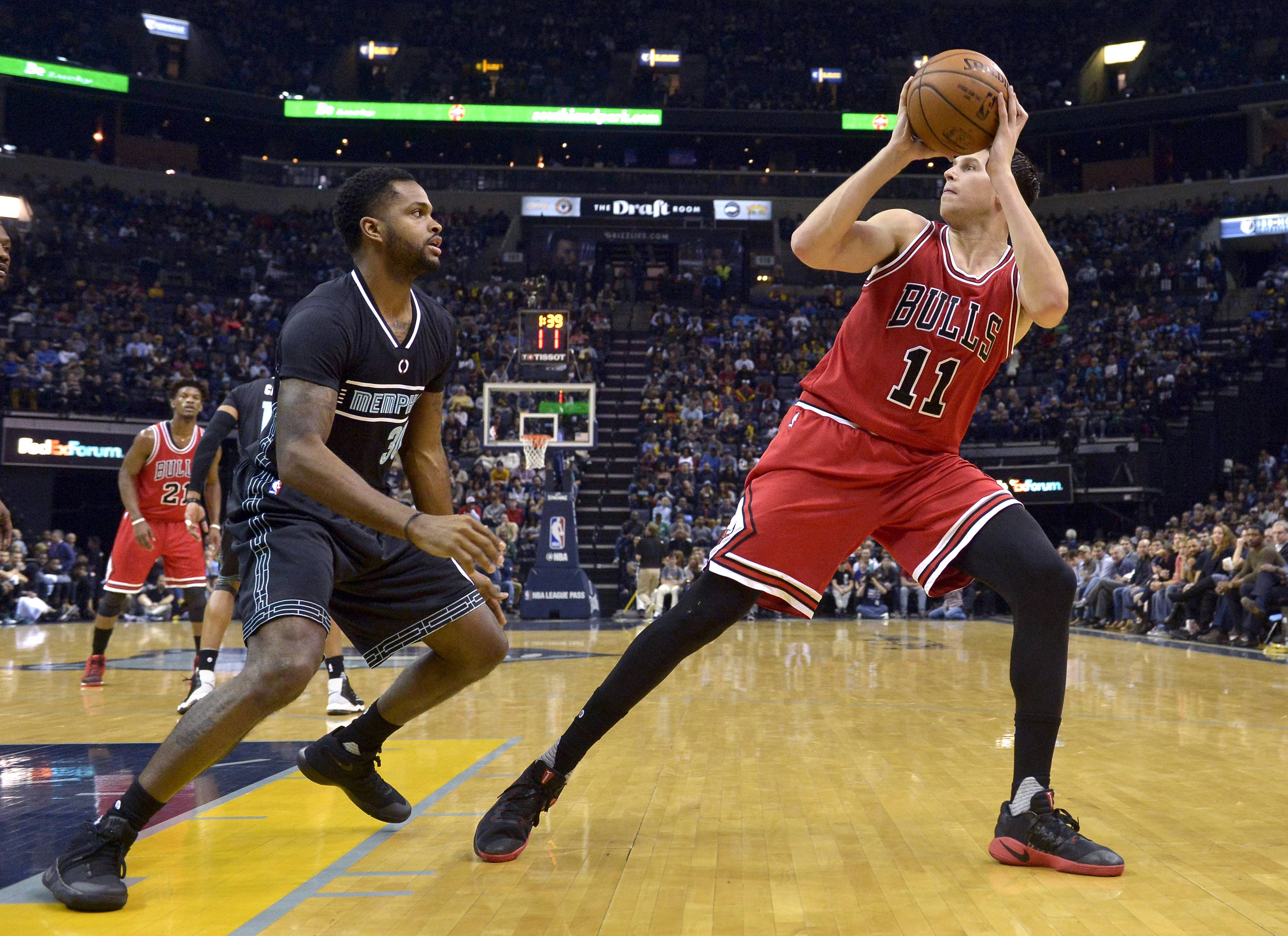 Bulls forward Doug McDermott turns to shoot against Grizzlies guard Troy Daniels in the second half of Sunday's game in Memphis.