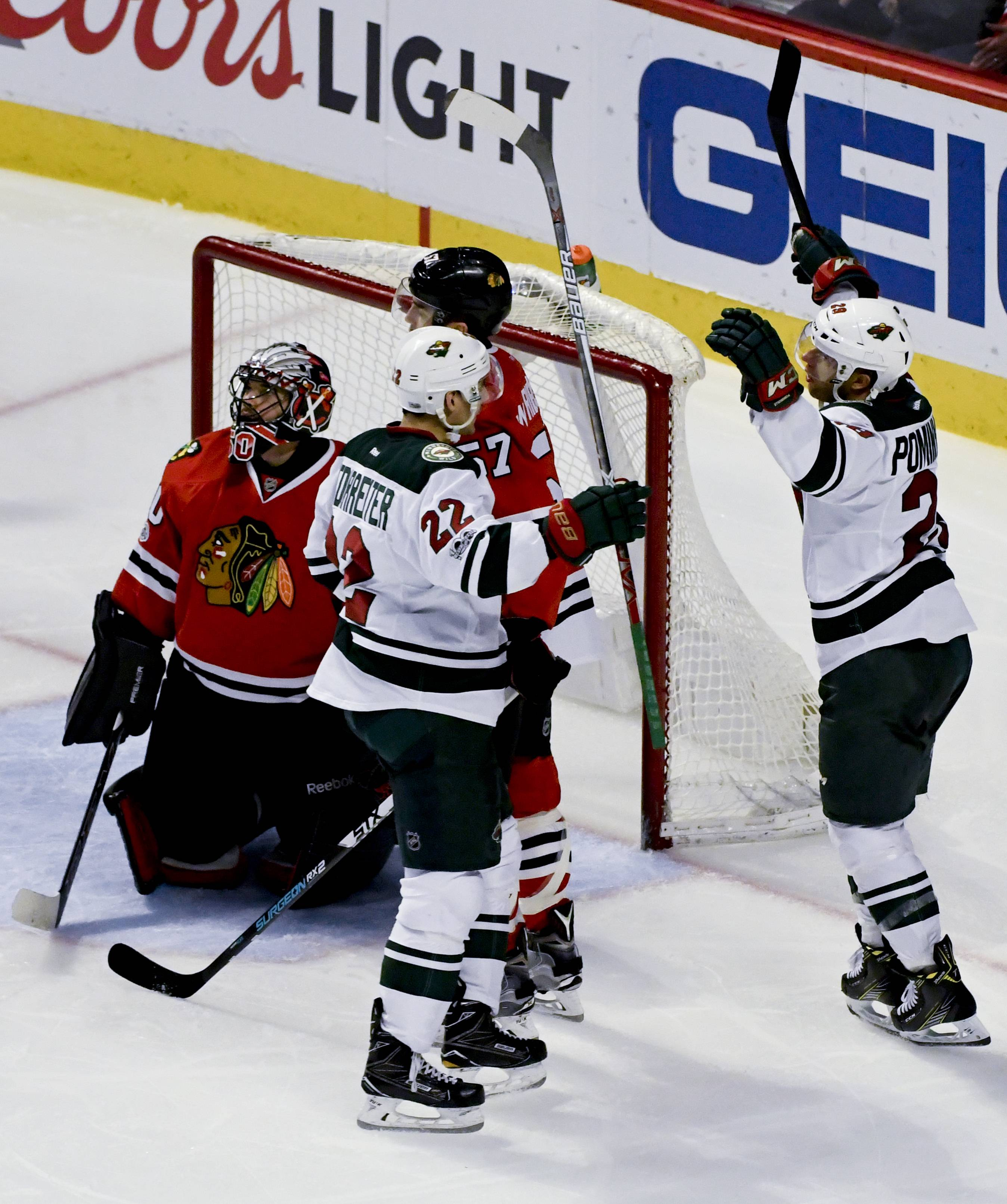Chicago Blackhawks goalie Corey Crawford (50) and Trevor van Riemsdyk , center, look on as Minnesota Wild right wing Nino Niederreiter (22) and right wing Jason Pominville, right, celebrate after he scored the game winning goal during the third period of an NHL hockey game on Sunday, Jan. 15, 2017, in Chicago. (AP Photo/Matt Marton)