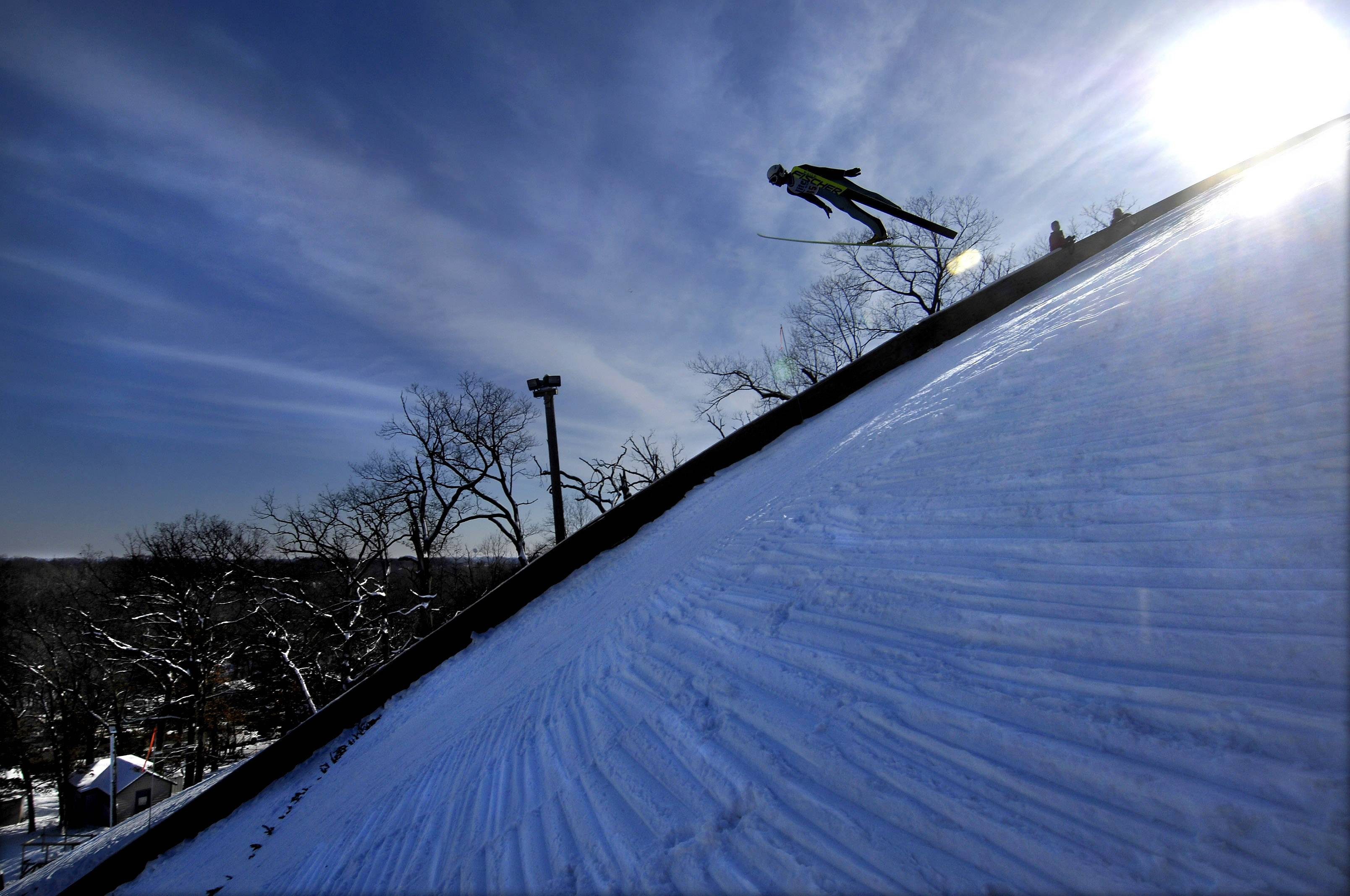 The packed snow on the 70-meter ski jump hill reflects the blue winter sky as Blake Hughs sails down at the annual Norge Ski Club winter jump competition in Fox River Grove. Dozens of former and potential Olympic ski jumpers compete at the event, which kicks off this weekend for the 112th year.
