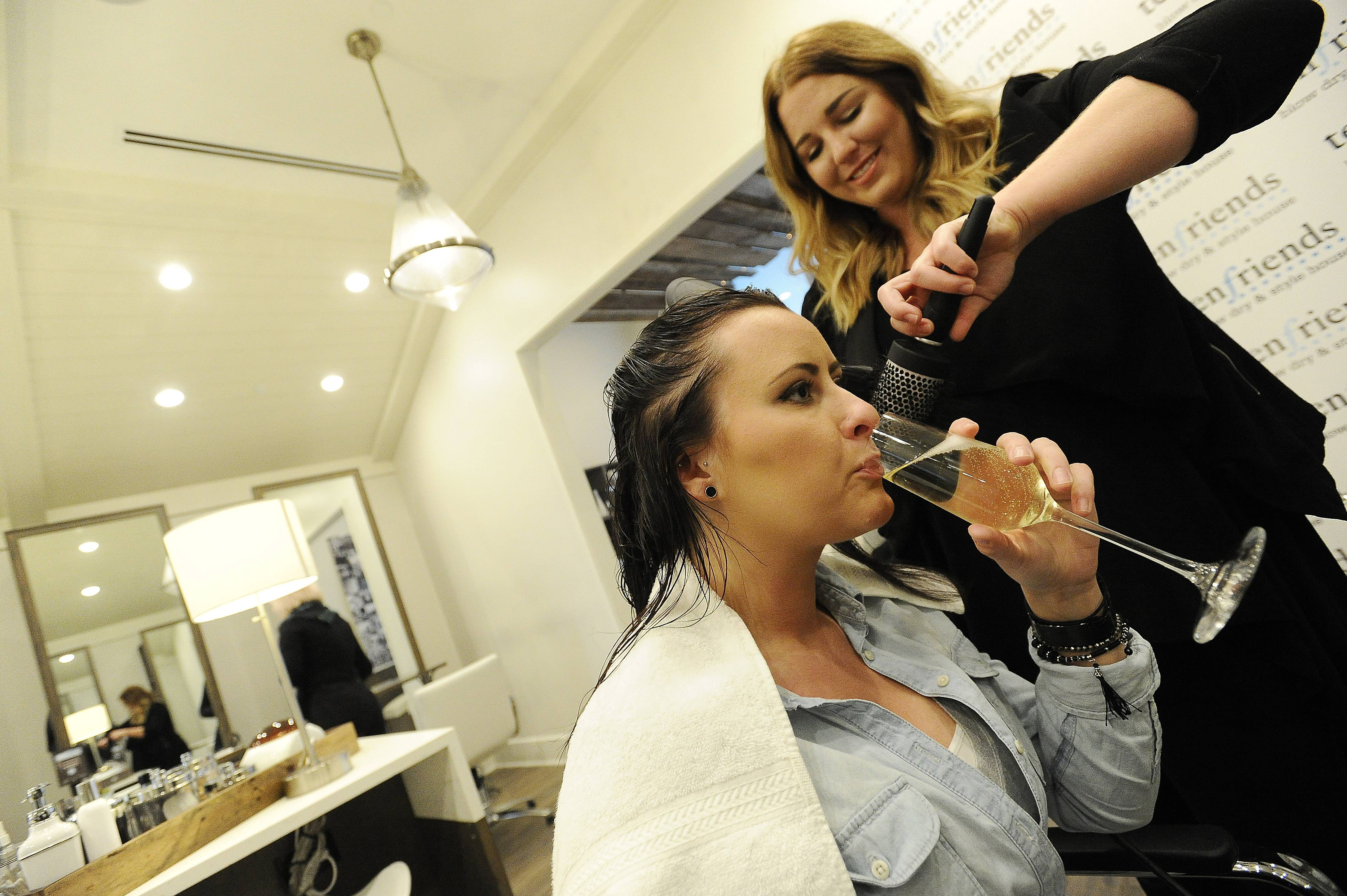 Deer Park's 10 Friends stylist Kelsey Pizur, 26, of Wauconda works on the hair of Amanda Bogard, 24, of Wauconda as she drinks a glass of champagne. The patrons have a choice of champagne or beer.