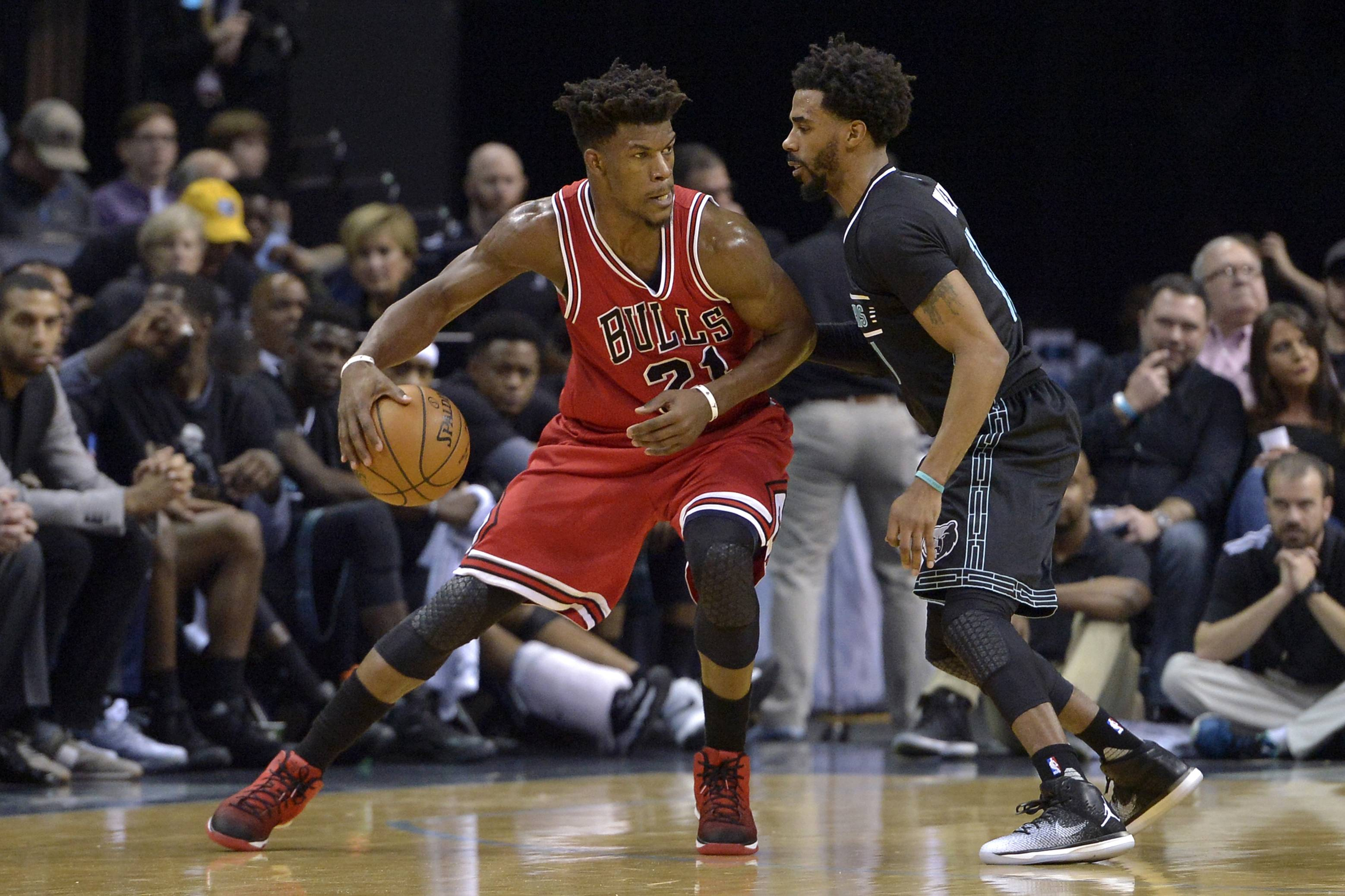 Chicago Bulls forward Jimmy Butler (21) controls the ball against Memphis Grizzlies guard Mike Conley in the first half of an NBA basketball game Sunday, Jan. 15, 2017, in Memphis, Tenn. (AP Photo/Brandon Dill)