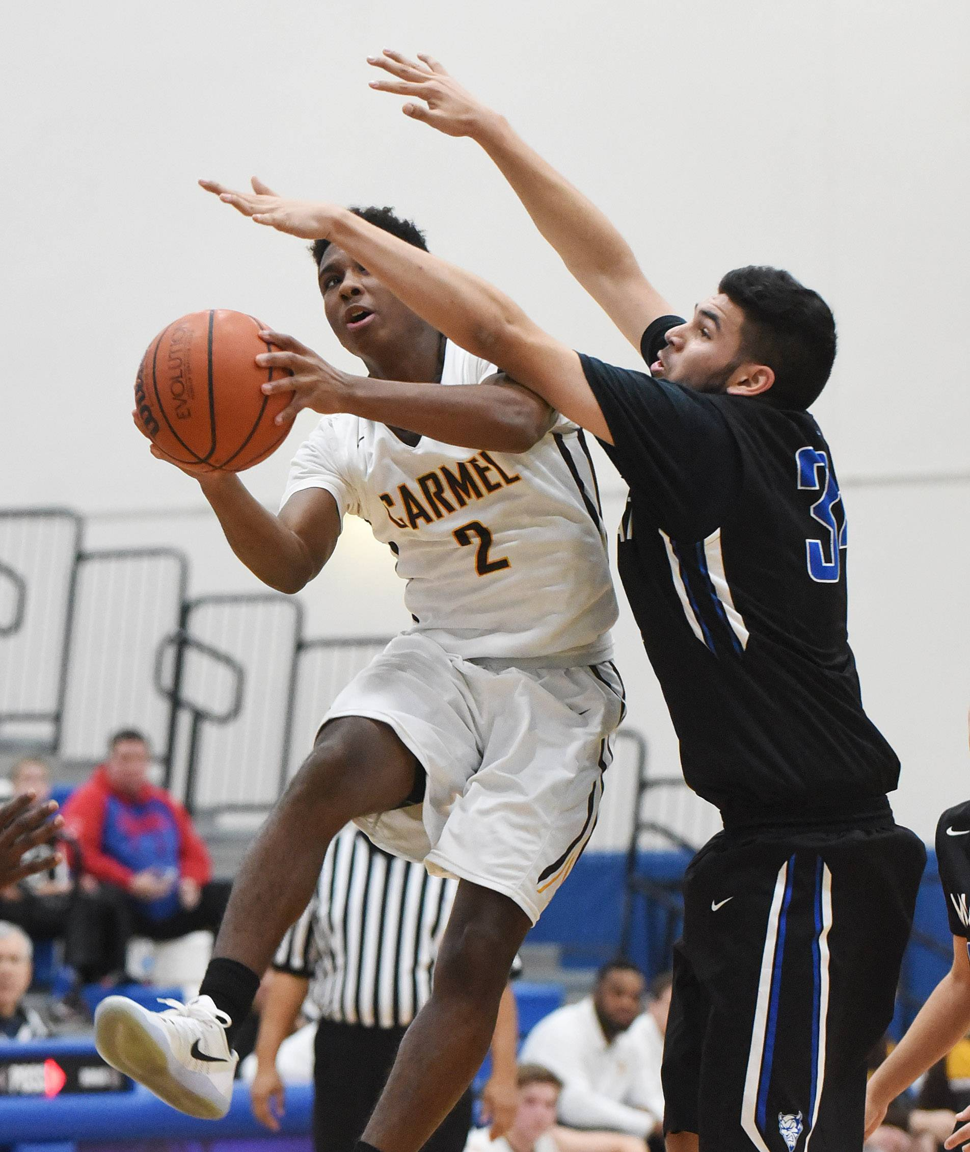 Carmel's Brian Julien (2) heads to the hoop past Maine East's Kyle Gilani during the MLK boys basketball tournament at Lake Zurich High School on Monday.