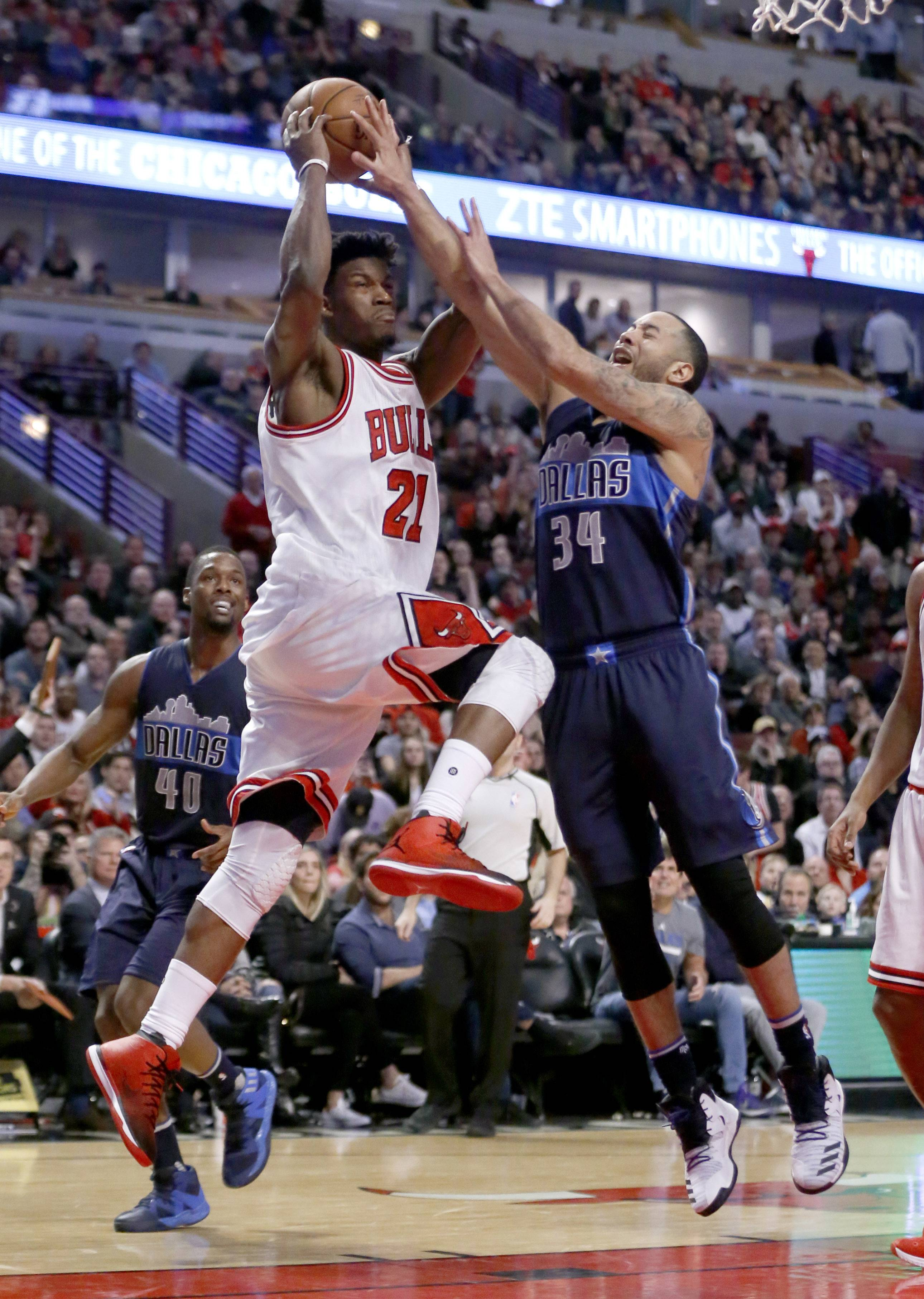 Chicago Bulls' Jimmy Butler (21) drives it the basket and is fouled by Dallas Mavericks' Devin Harris during the second half of an NBA basketball game Tuesday, Jan. 17, 2017, in Chicago. The Mavericks won 99-98. (AP Photo/Charles Rex Arbogast)