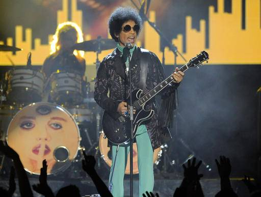 FILE - In this May 19, 2013 file photo, Prince performs at the Billboard Music Awards at the MGM Grand Garden Arena in Las Vegas. The Minnesota judge overseeing Prince's estate holds a hearing Thursday, Jan. 12, 2017, on whether to declare his siblings as his heirs, and who should manage the rock superstar's estate going forward. No will has surfaced since Prince died of an accidental painkiller overdose in April 2016. (Photo by Chris Pizzello/Invision/AP, File)