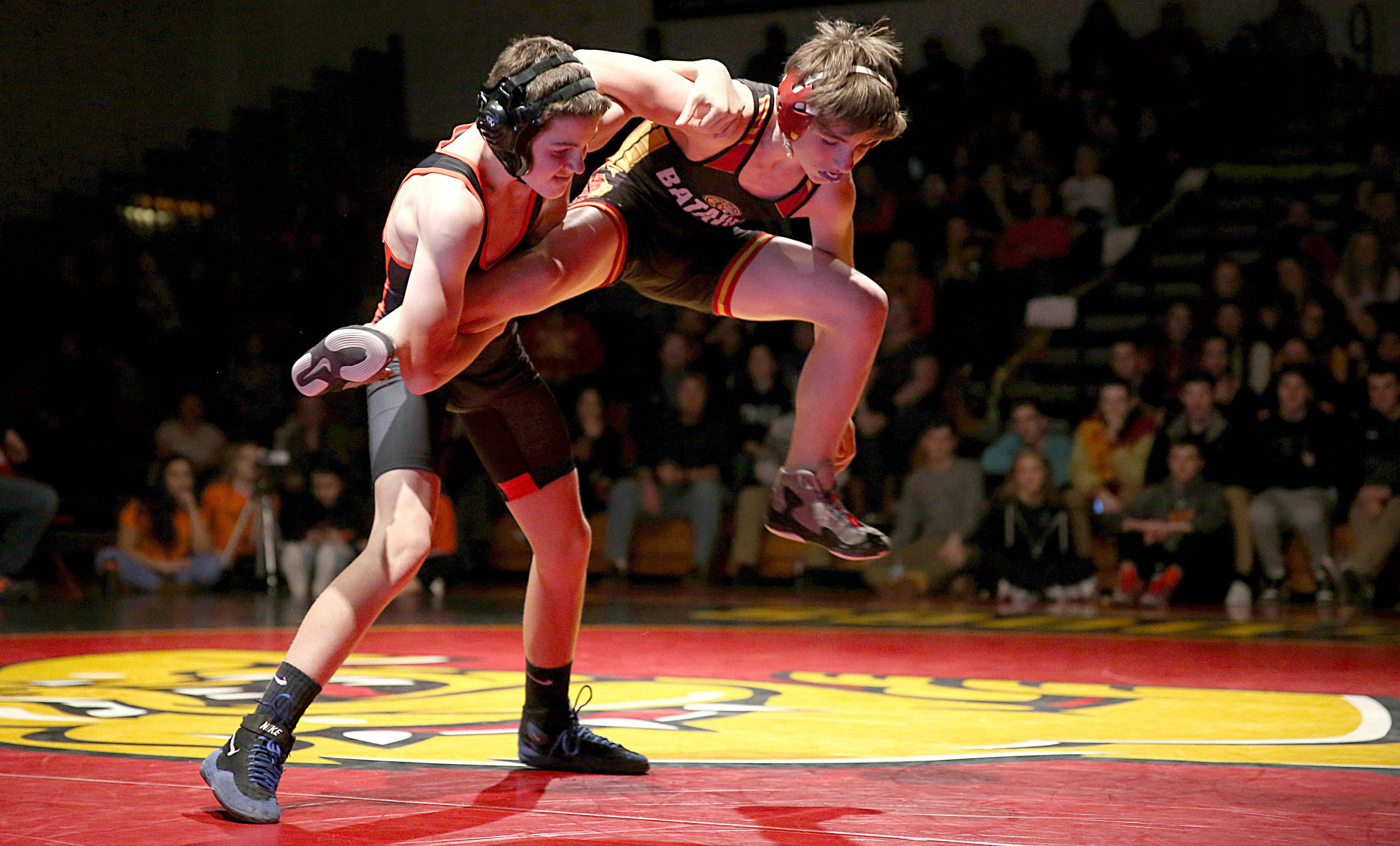 St. Charles East's Peyton Schroeder, left, battles as Batavia's Nick Pierce hops off the mat at 106 pounds during a varsity wrestling meet at Batavia Tuesday night.