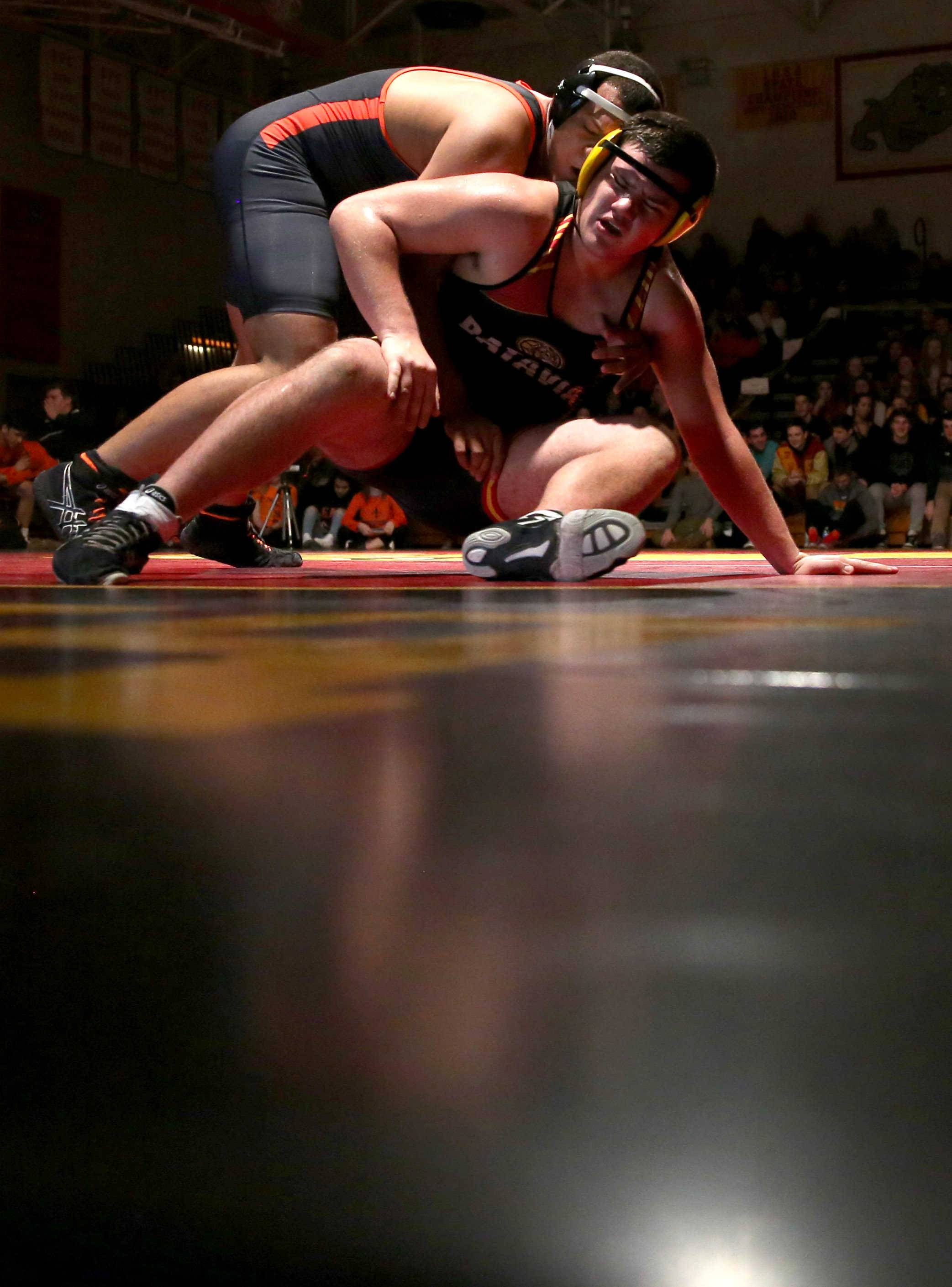 St. Charles East's Darrell Gregg battles Batavia's Jack Darby, front, at 220 pounds during a varsity wrestling meet at Batavia Tuesday night.