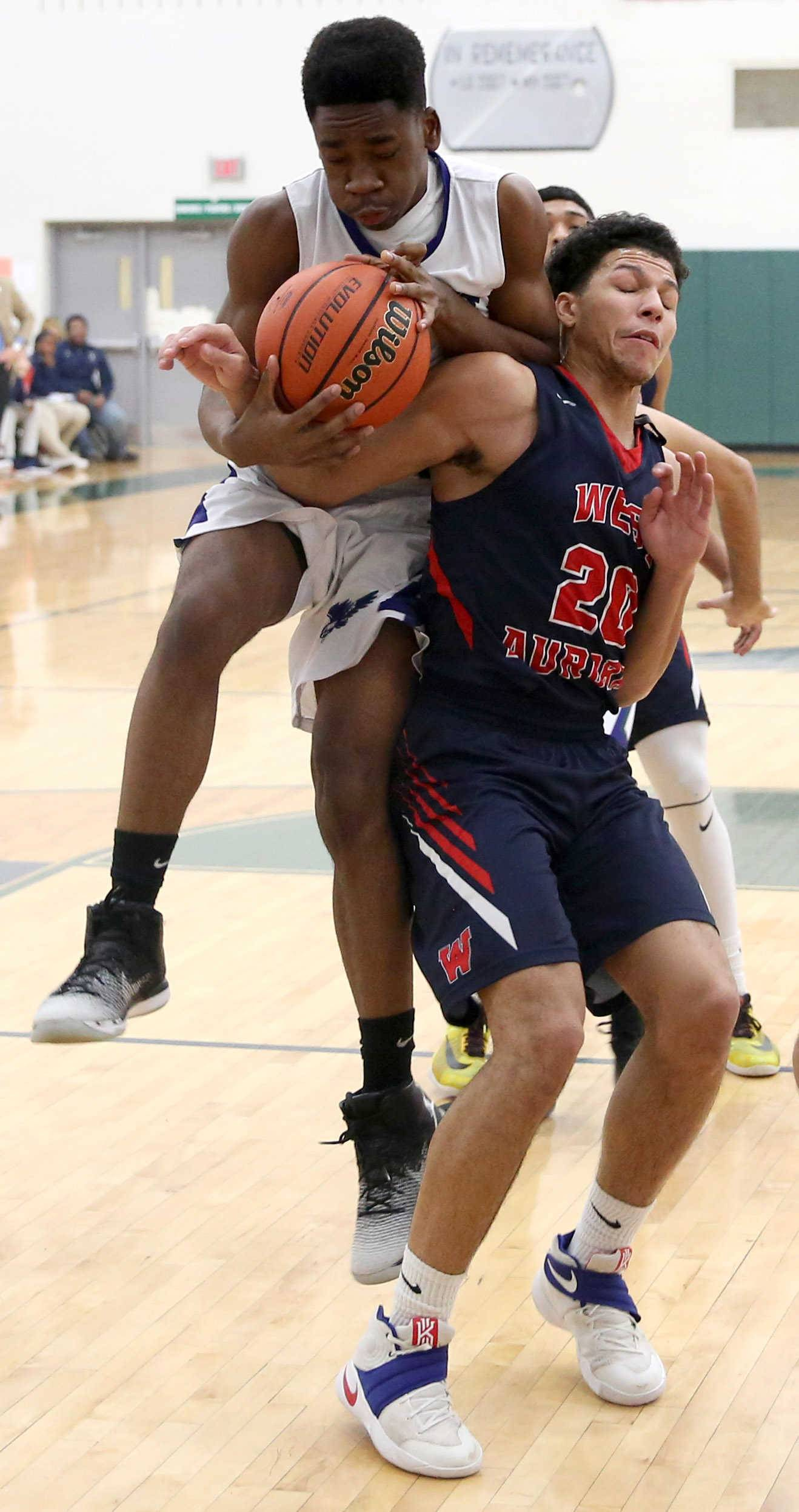 Bartlett's Jake Ibegbulem, left, gets tangled up with West Aurora's Caleb Siler during varsity boys basketball at Bartlett Wednesday night.