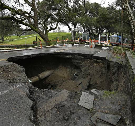 A 72-inch deep sinkhole is seen Wednesday, Jan. 18, 2017, in Orinda, Calif. The city council of Orinda declared a State of Emergency Tuesday night because of a large sinkhole caused by last week's wet weather, which ruptured two sewer lines. Repairs will take at least four weeks, as the San Francisco Bay Area is being hit with a new series of rain storms. (AP Photo/Ben Margot)