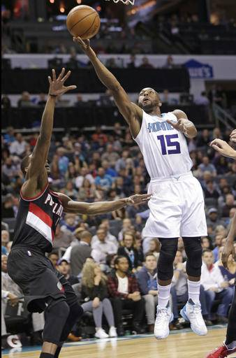 Charlotte Hornets' Kemba Walker (15) shoots over Portland Trail Blazers' Damian Lillard (0) during the first half of an NBA basketball game in Charlotte, N.C., Wednesday, Jan. 18, 2017. (AP Photo/Chuck Burton)