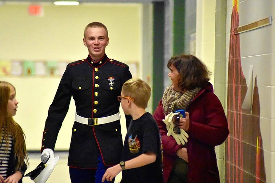 Once a student, now a Marine, Reid Luczak, Laurie Luczak, and little brother Jace Luczak make their way to Lisa Morello's fifth-grade classroom.