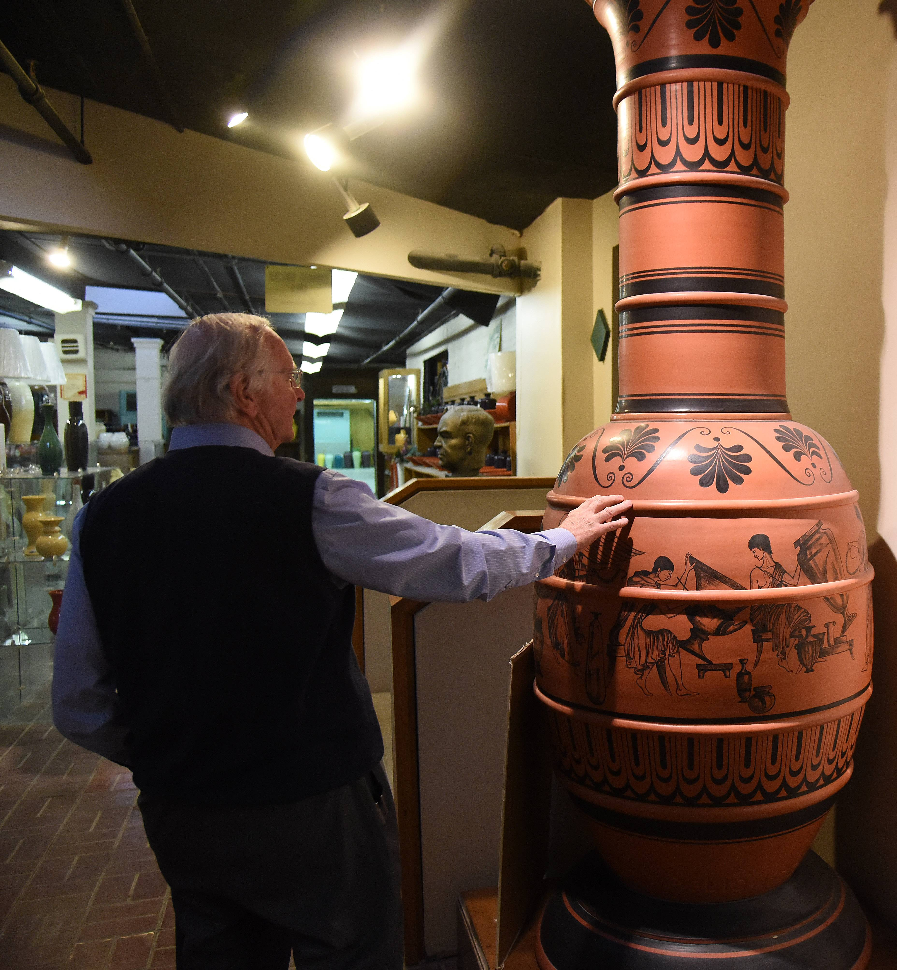 Craig Zachrich, chief operating officer of Haeger Potteries, shows off what was once the world's largest hand-thrown pot at their East Dundee store shortly after the 145-year-old company announced it was closing. The 92-inch-tall vase is up for auction next month and is expected to be sold for $6,000 to $8,000.
