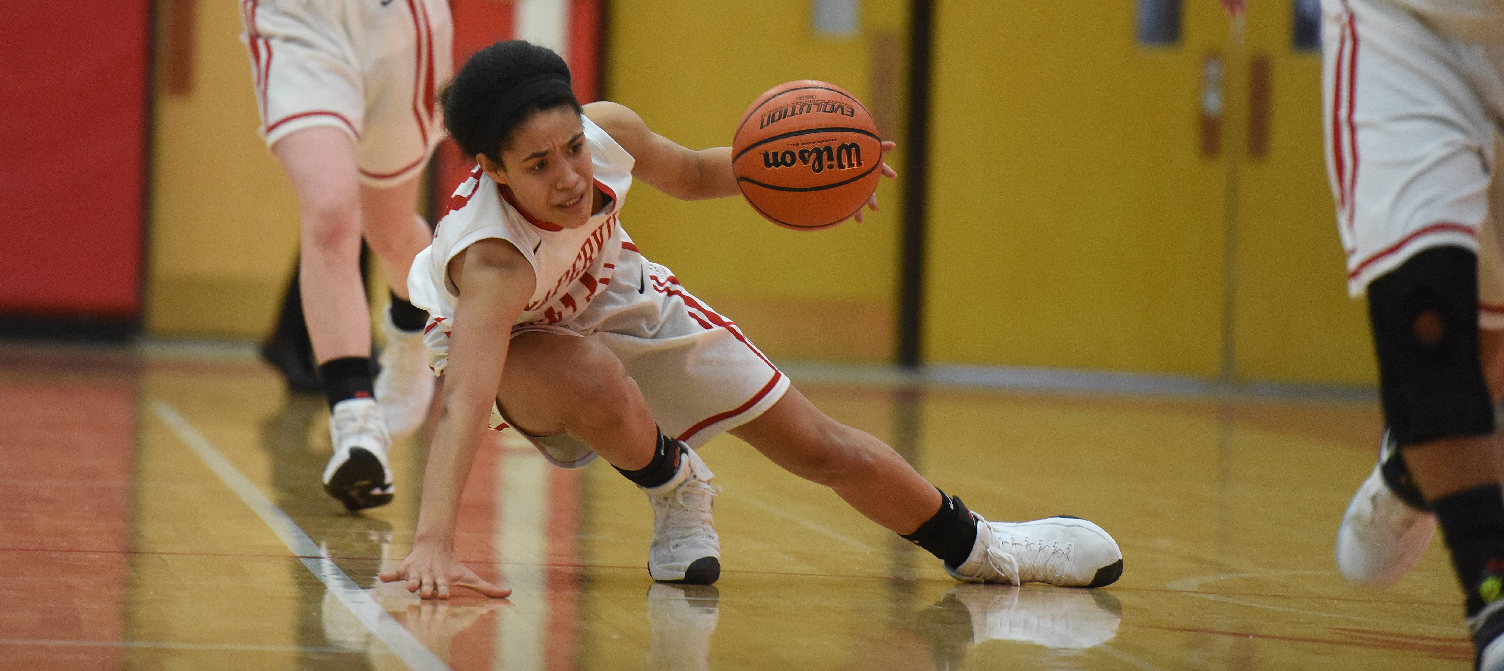 Naperville Central's Mia Lakstigala drives the ball during the Metea Valley at Naperville Central girls basketball game Thursday.