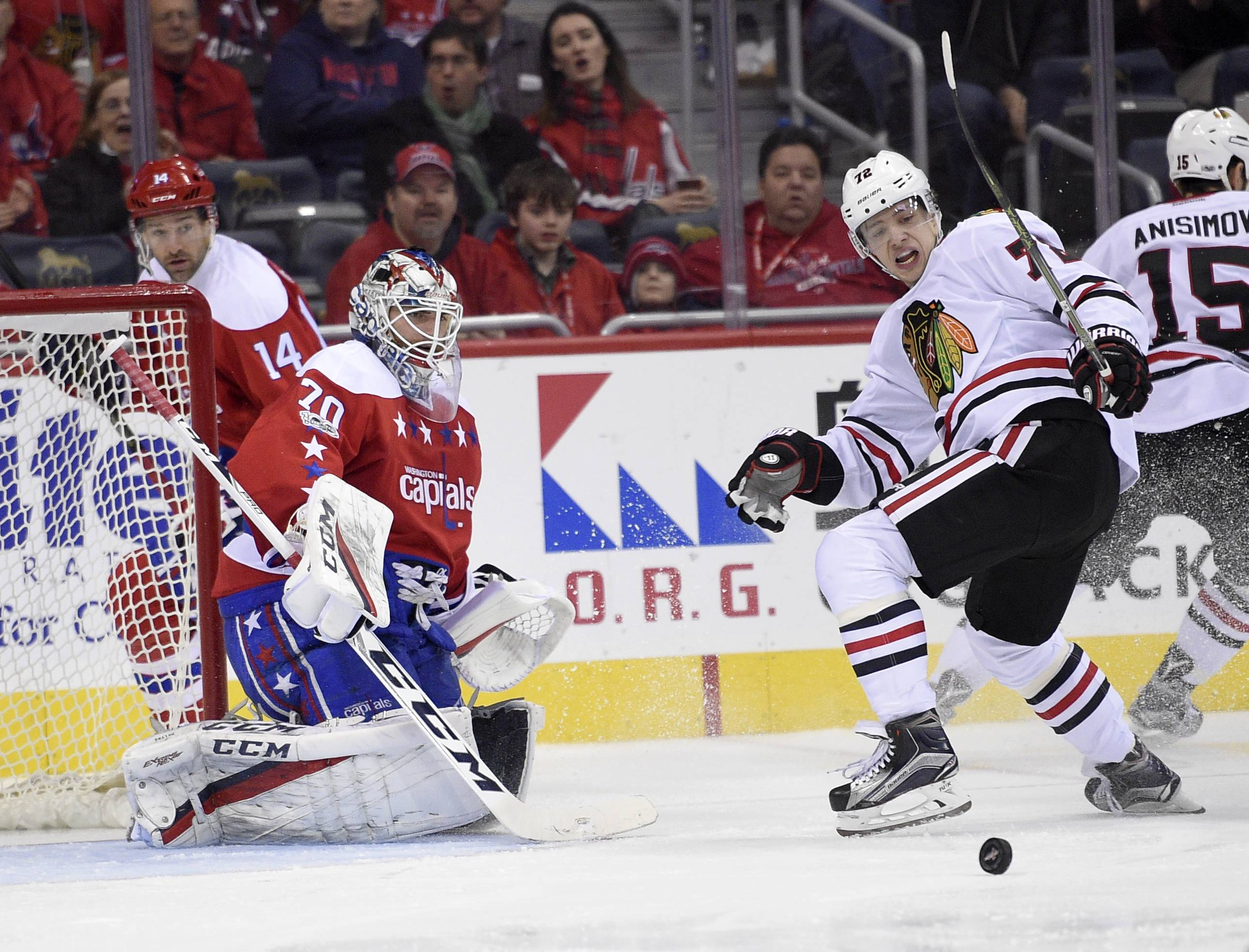 Chicago Blackhawks left wing Artemi Panarin (72), of Russia, and Washington Capitals goalie Braden Holtby (70) watch the puck during the third period of an NHL hockey game, Friday, Jan. 13, 2017, in Washington. The Capitals won 6-0. (AP Photo/Nick Wass)