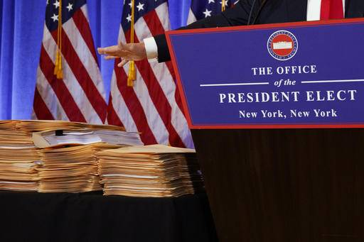 "FILE - In this Wednesday, Jan. 11, 2017, file photo, President-elect Donald Trump gestures next to stacks of manila envelopes he says contain documents formalizing new business arrangements, while speaking during a news conference in the lobby of Trump Tower in New York. Trump has vowed his company will do ""no new foreign deals� while he is president, but he left vague just how to define ""new� and ""deals.� (AP Photo/Evan Vucci, File)"