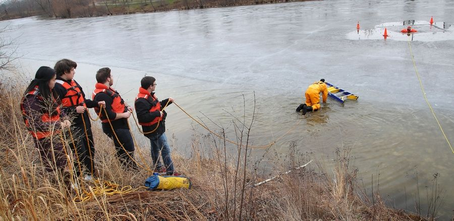 Students hold safety ropes as Kyle Schrems of the Countryside Fire Protection District crawls out on a frozen pond to rescue Vernon Hills High School teacher Jerry Miceli, right, during a demonstration Thursday.