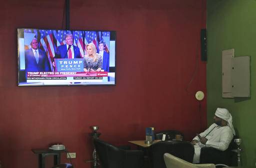 FILE - In this Thursday, Nov. 10, 2016 file photo, an Emirati man smokes a water pipe while watching coverage of President-elect Donald Trump at a coffee shop in Dubai, United Arab Emirates. Donald Trump's all-but-dismissal of human rights as a foreign policy principle could profoundly shake a Middle East landscape beset by warring factions and beleaguered governments, with some players eyeing once unimaginable new alliances. Syria is the foremost test of Trump's promise of a return to hard-headed realpolitik and could quickly show whether America is truly abandoning promotion of democracy and the rule of law in a way that could reshape the region's order. (AP Photo/Kamran Jebreili, File)
