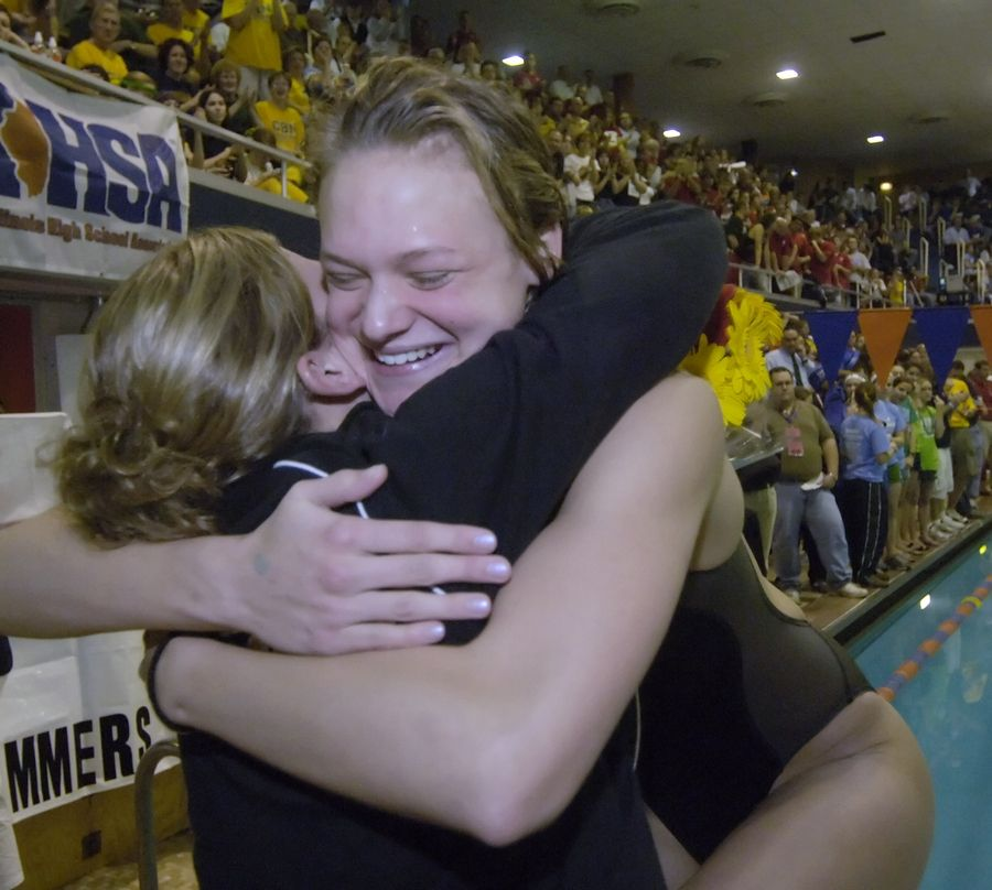 Stevenson's Ashley Wanland, right, gets a hug from her sister, Aubrey, after winning the 100-yard breaststroke during the girls swimming state meet at Evanston.