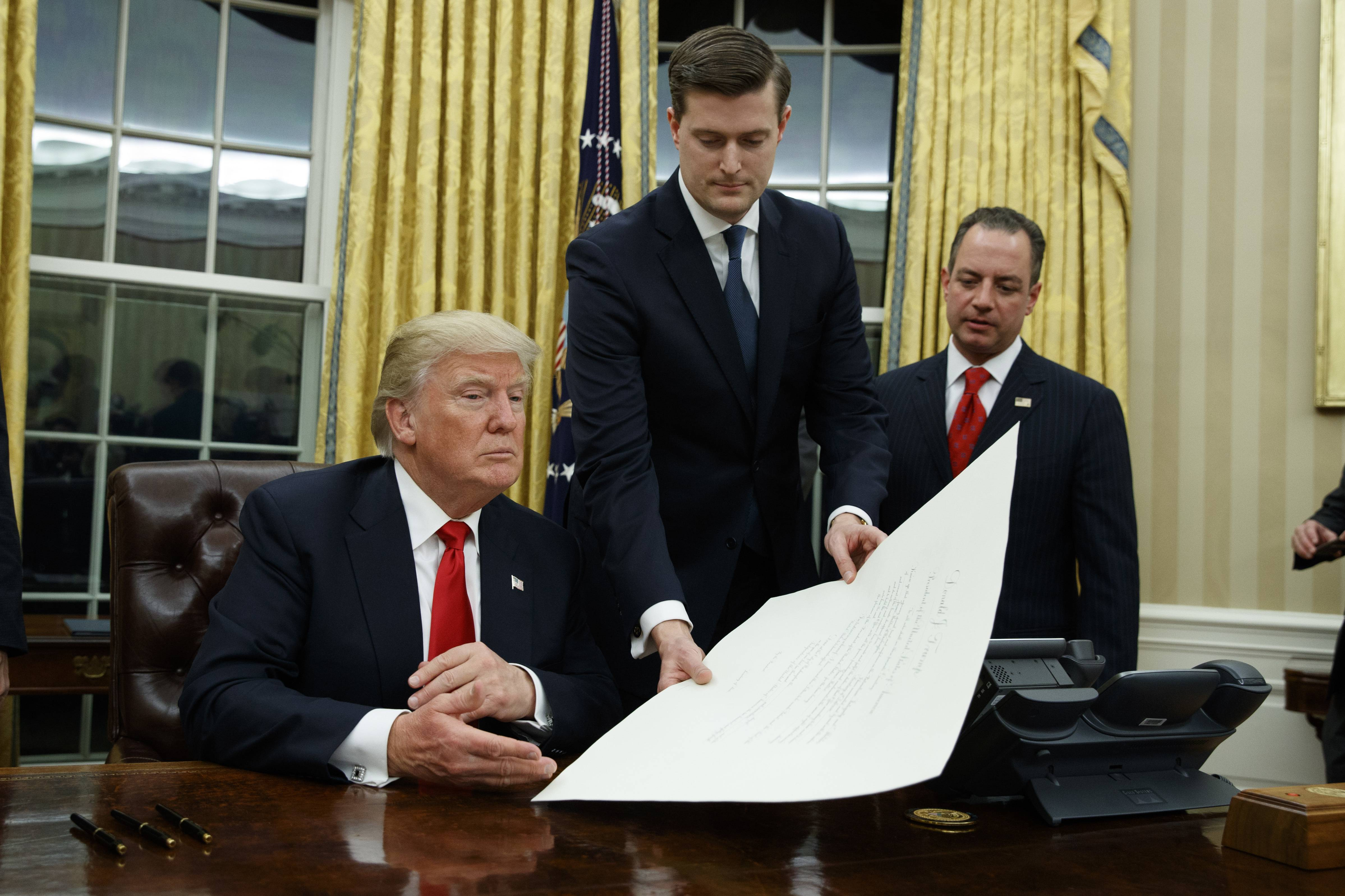 White House Chief of Staff Reince Priebus, right, watches as White House Staff Secretary Rob Porter, center, hands President Donald Trump a confirmation order for James Mattis as defense secretary Friday in the Oval Office of the White House in Washington.