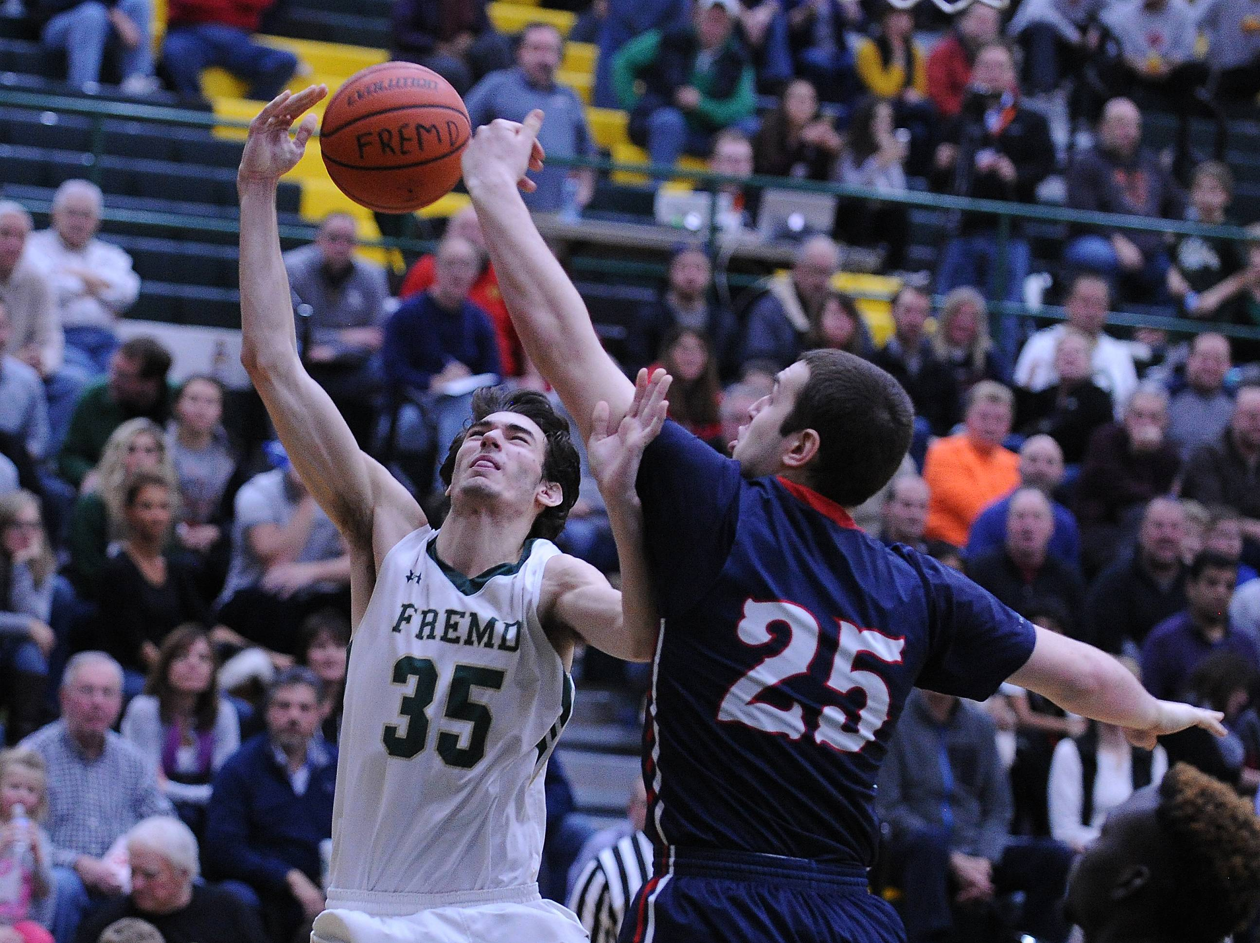 Conant's Ryan Davis slaps the ball away from Fremd's Brian Dompke as he drives for the basket in boys varsity basketball action at Fremd on Friday.