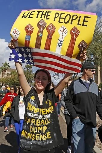 A demonstrator holds a sign as she marches in support of the Women's March on Washington Saturday, Jan. 21, 2017, in Phoenix. Thousands of protesters in Phoenix joined in support of those in cities around the globe protesting against Donald Trump as the new United States president.