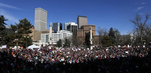 Anti-Trump crowds chant and raise home-made signs during a women's march and rally in Denver, Saturday, Jan. 21, 2017. The march was held in solidarity with similar events taking place in Washington and around the nation. (AP Photo/Brennan Linsley)2