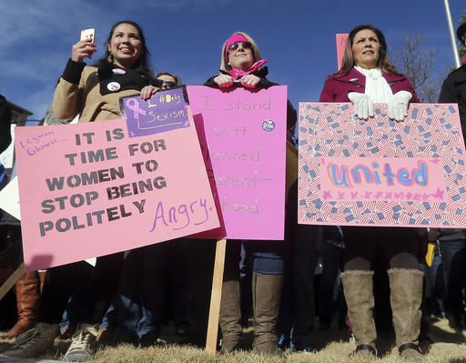 Roxanne Vigil, from left, Heather Murth and Janette Vigil, listen to a speech in front of the Wyoming Supreme Court during the Women's March Saturday morning, Jan. 21, 2017, in downtown Cheyenne, Wyo. Several thousand people took park in the march to focus on the rights of women and other minority and disadvantaged groups.  (Blaine McCartney/The Wyoming Tribune Eagle via AP)