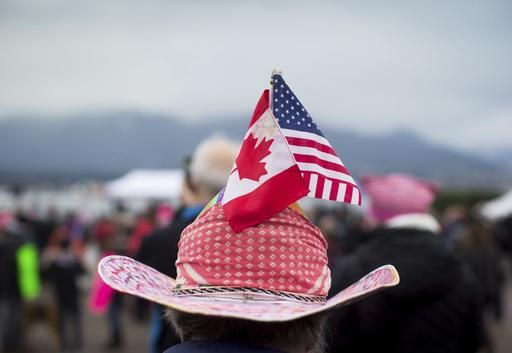 A woman sports Canadian and U.S. flags on her hat during a women's march and protest against U.S. President Donald Trump, in Vancouver, British Columbia on Saturday Jan. 21, 2017. Protests are being held across Canada today in support of the Women's March on Washington.   (Darryl Dyck/The Canadian Press via AP)