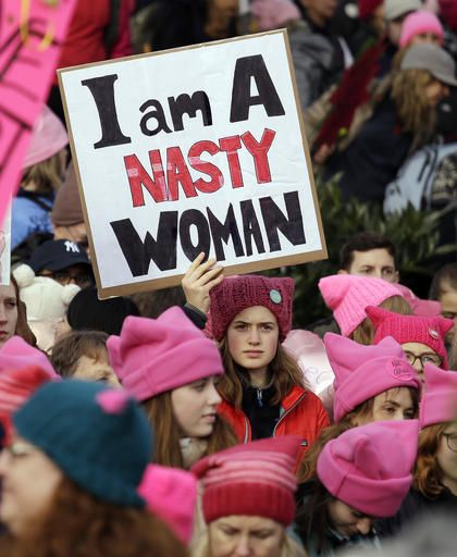 A woman holds a sign amidst a sea of pink caps before a women's march Saturday, Jan. 21, 2017, in Seattle. Women across the Pacific Northwest marched in solidarity with the Women's March on Washington and to send a message in support of women's rights and other causes.