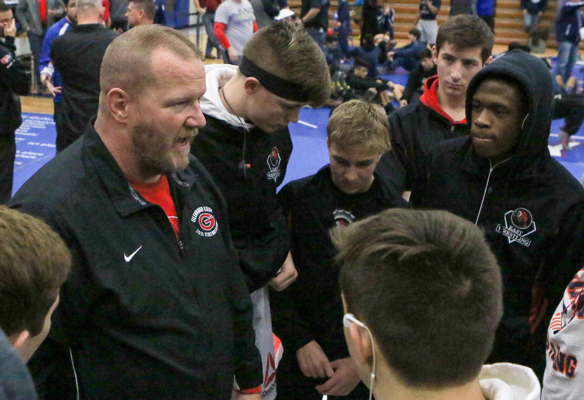 Glenbard East wrestling coach Kevin Carlson talks to his team during the Upstate Eight Conference meet at Larkin Saturday.