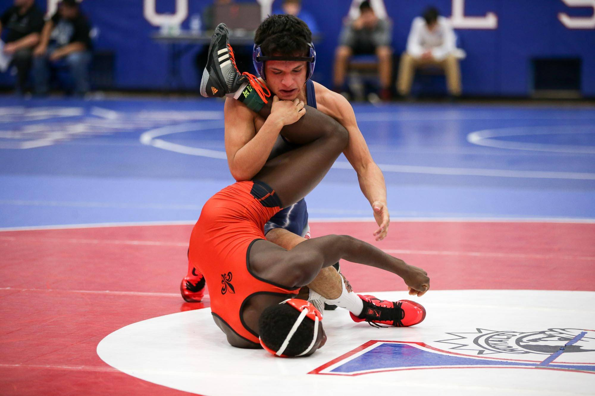 West Aurora's Issac Jacquez grabs the leg of St. Charles East's Lucson Schneider during their 126-pound final match at Larkin Saturday.