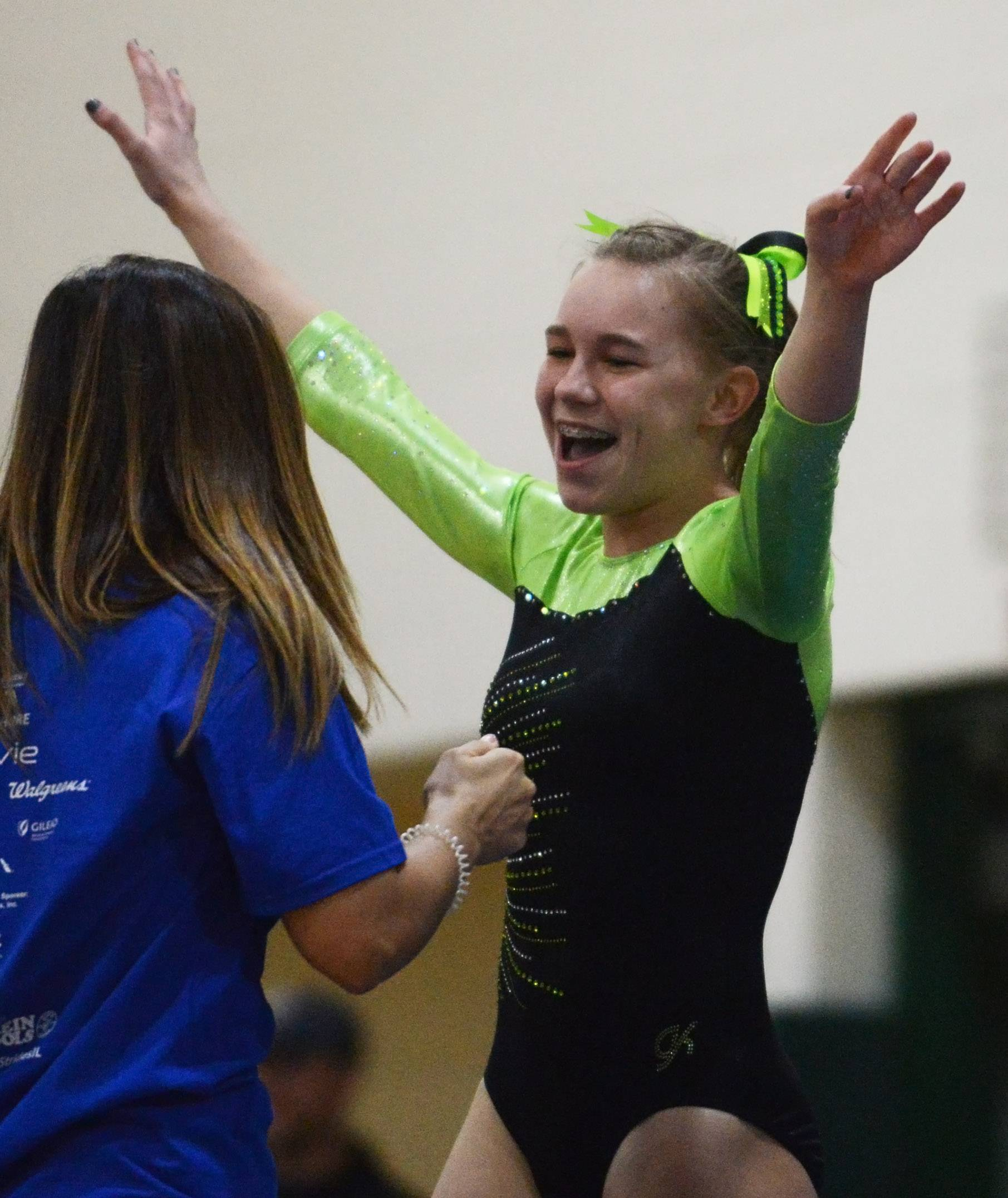 Fremd's Sam Shirmer celebrates her vault performance during the Fremd girls gymnastics invitational in Palatine on Saturday.