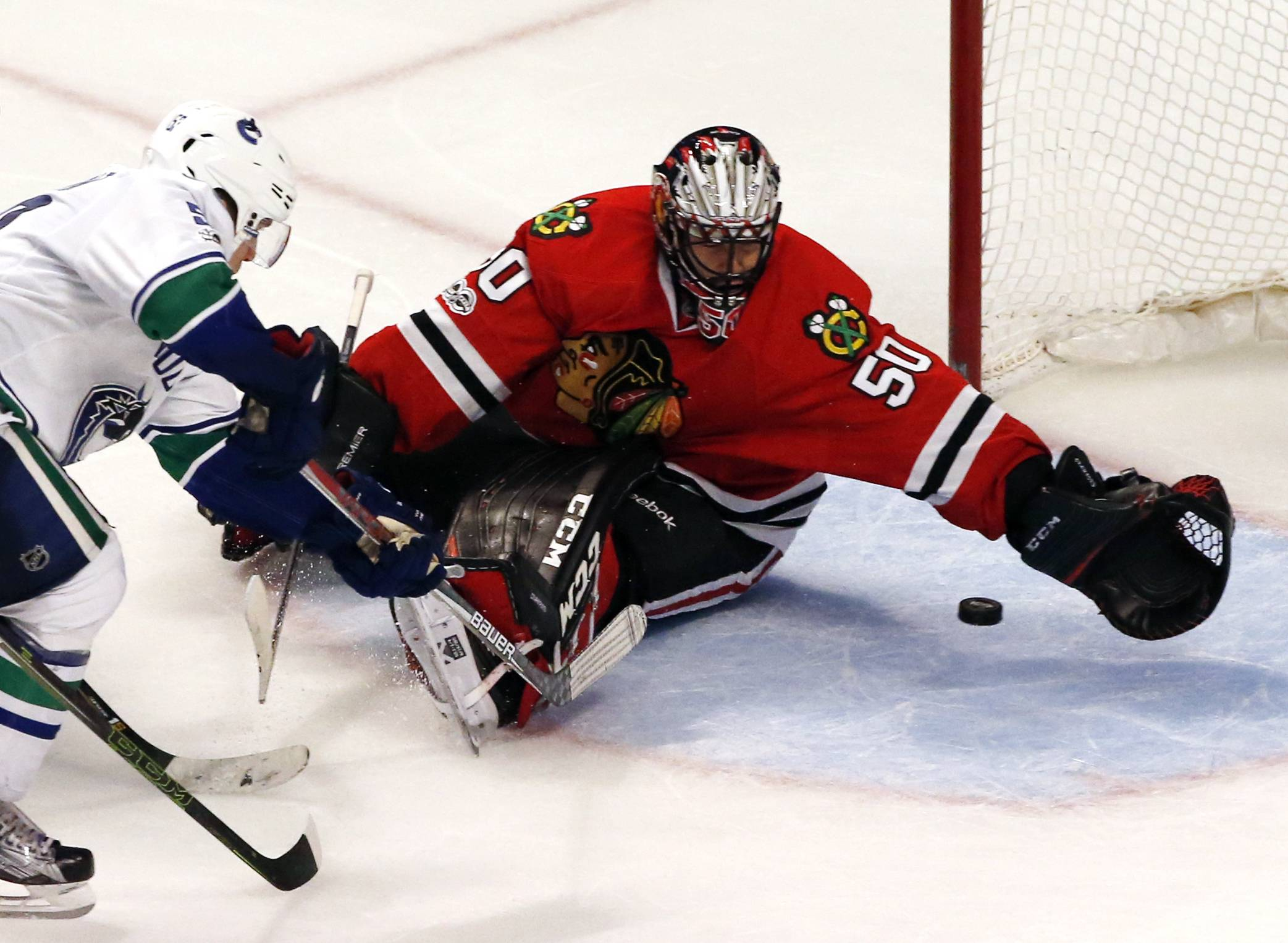 Vancouver Canucks center Bo Horvat, left, scores against Chicago Blackhawks goalie Corey crawford during the third period of an NHL hockey game, Sunday, Jan. 22, 2017, in Chicago. (AP Photo/Nam Y. Huh)