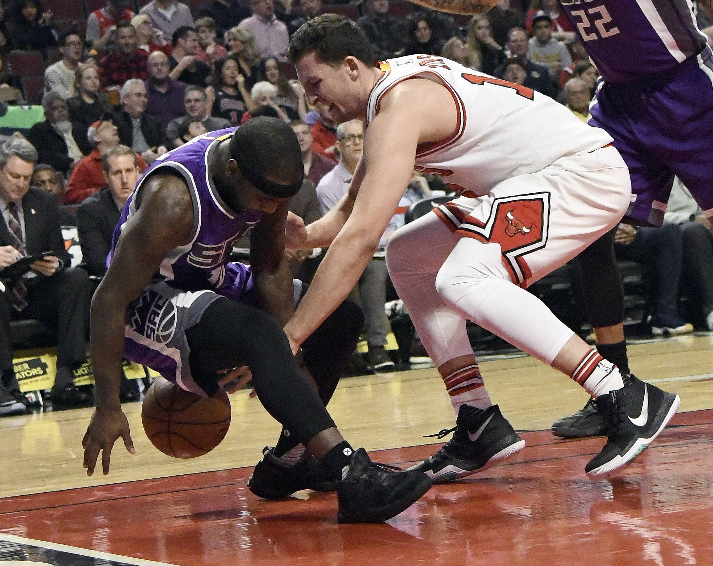 Sacramento Kings guard Ty Lawson, left, and Chicago Bulls forward Paul Zipser (16) go for a loose ball during the first half of an NBA basketball game in Chicago, Saturday, Jan. 21, 2017. (AP Photo/David Banks)